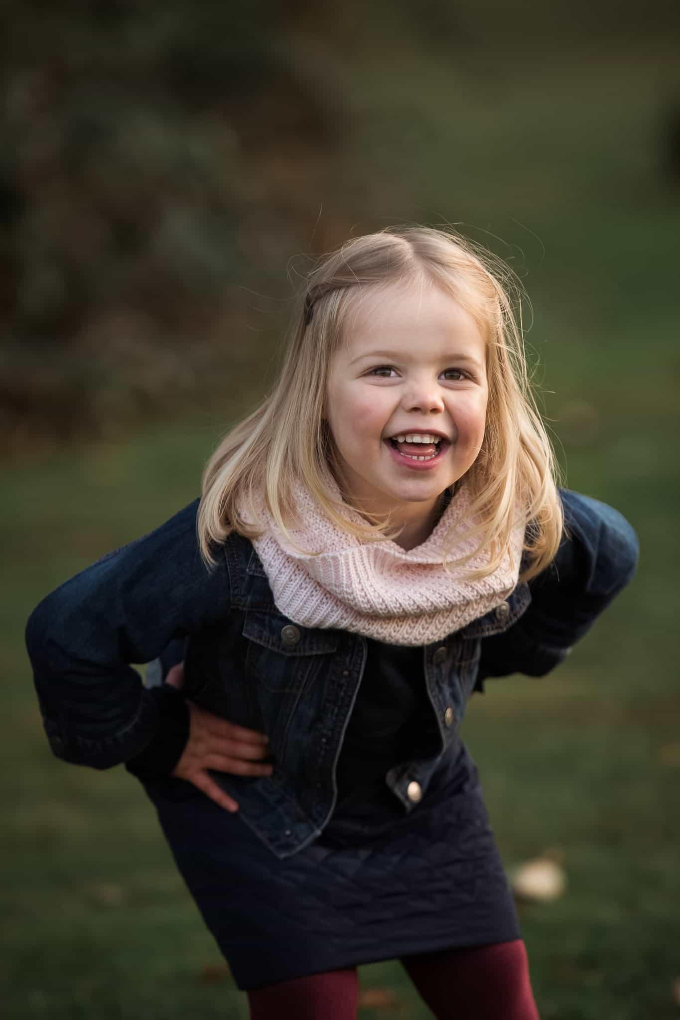 toddler girl bending over laughing
