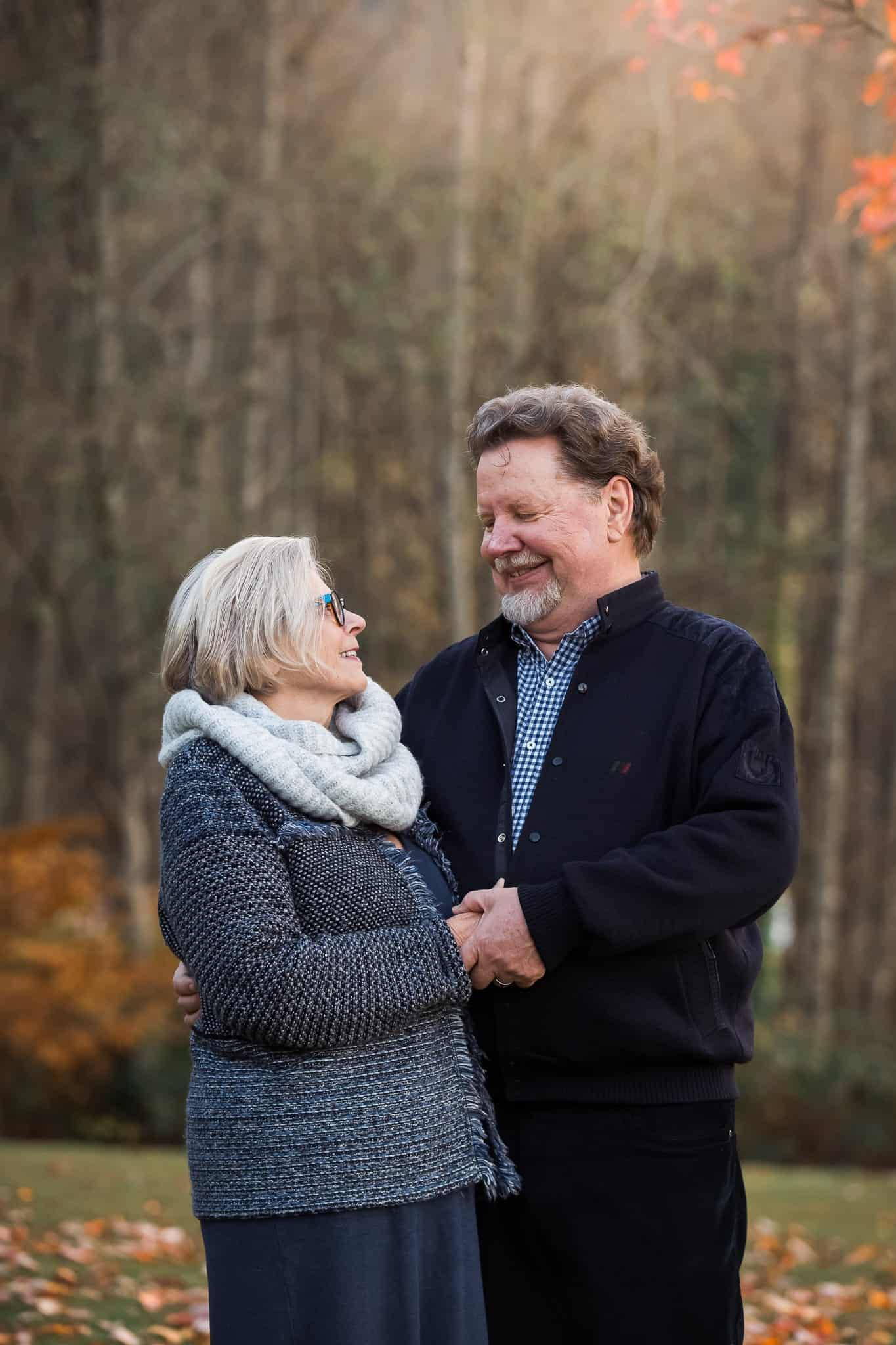 older couple holding hands and smiling at each other