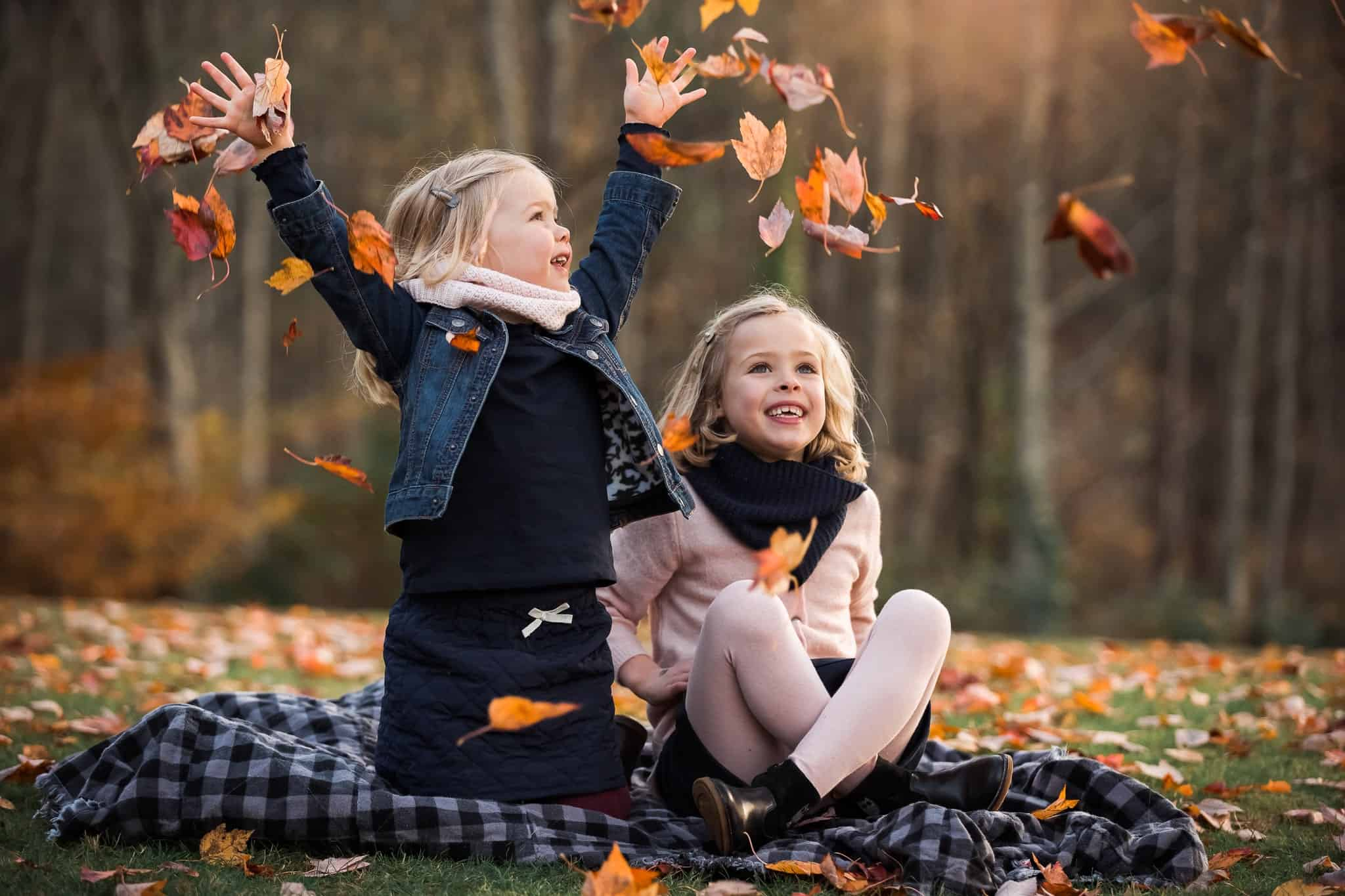 two little girls throwing leaves in the air