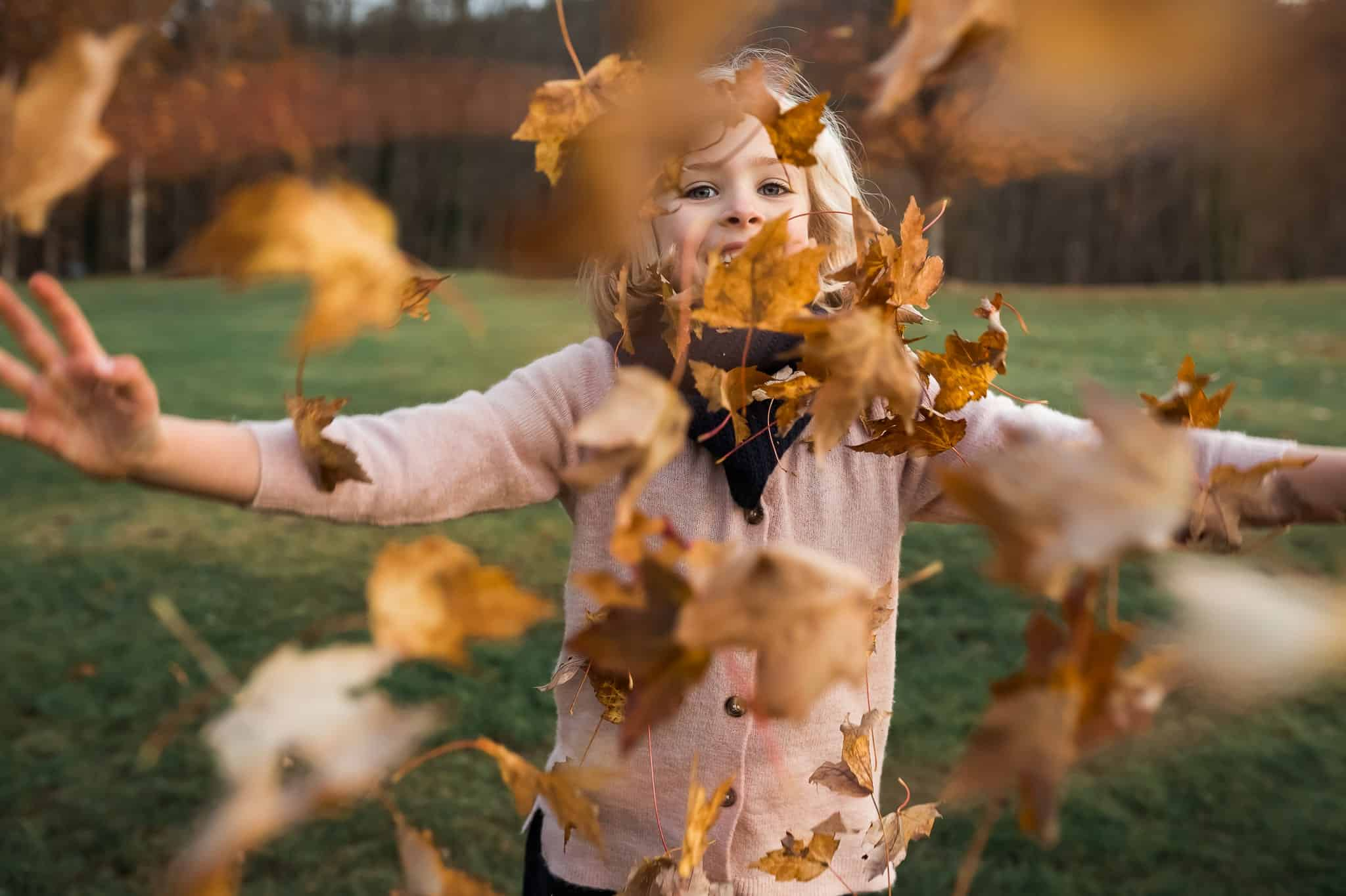 little girl throwing leaves at the camera
