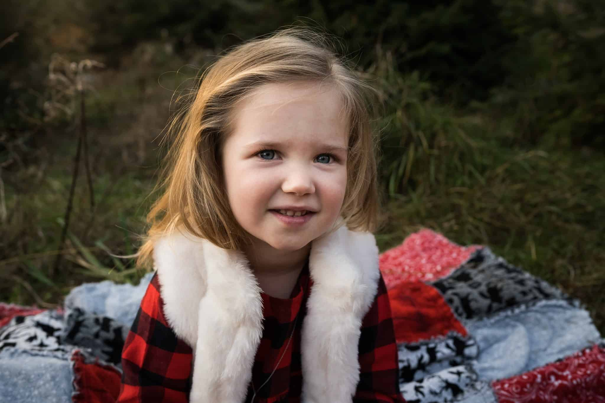 little girl sitting on Christmas blanket