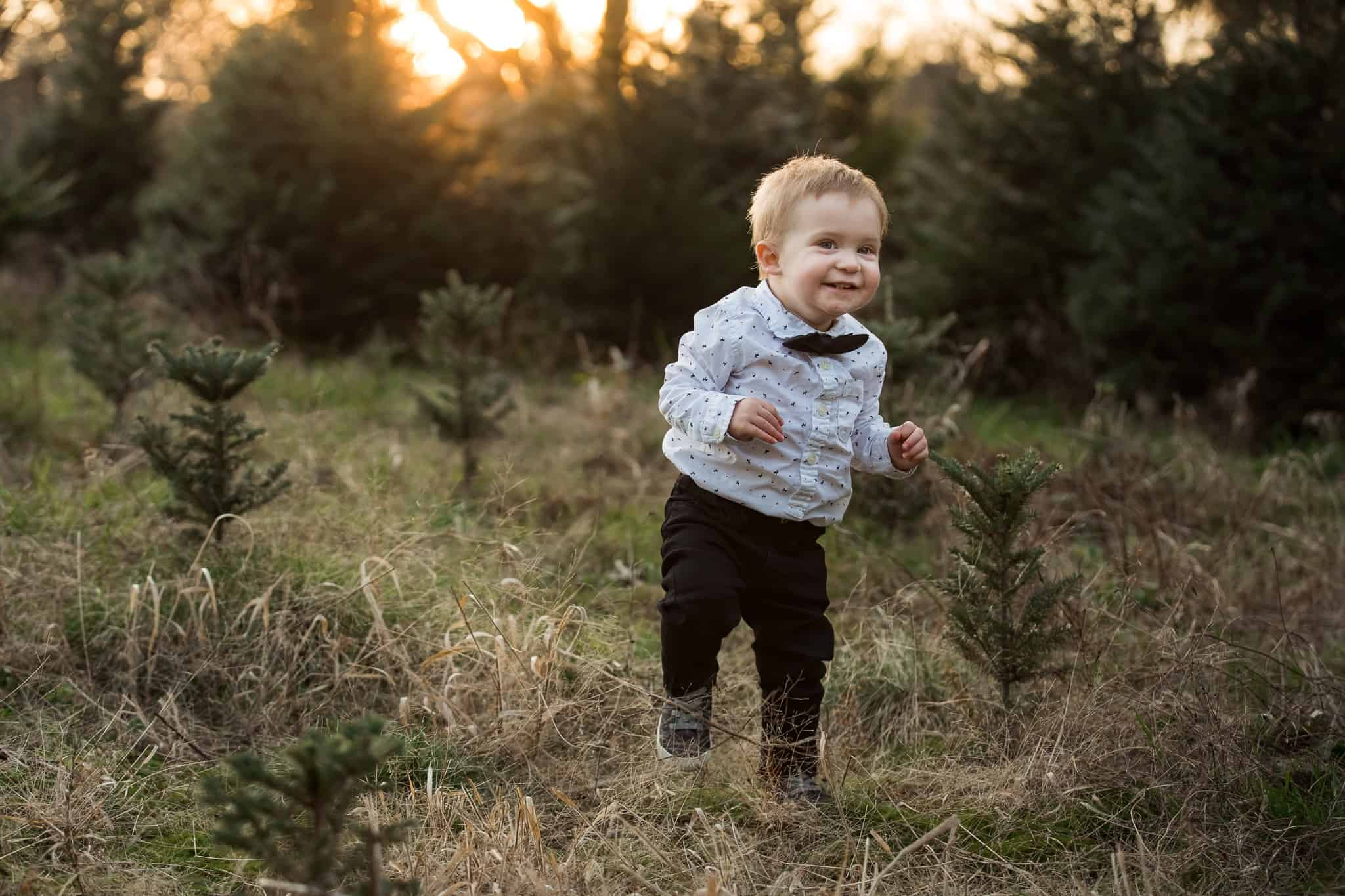 toddler boy in tiny tree forest with bowtie