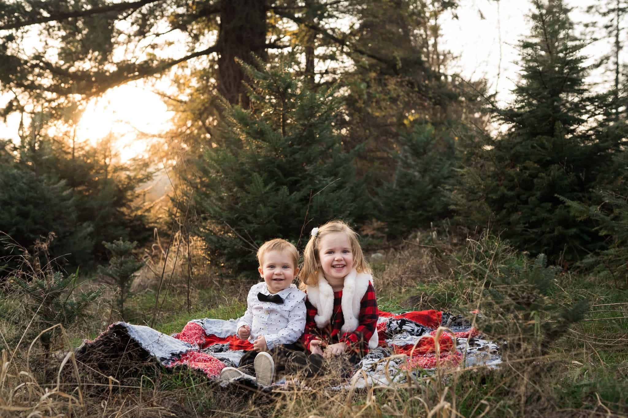 two little kids sitting on blanket in a forest at sunset