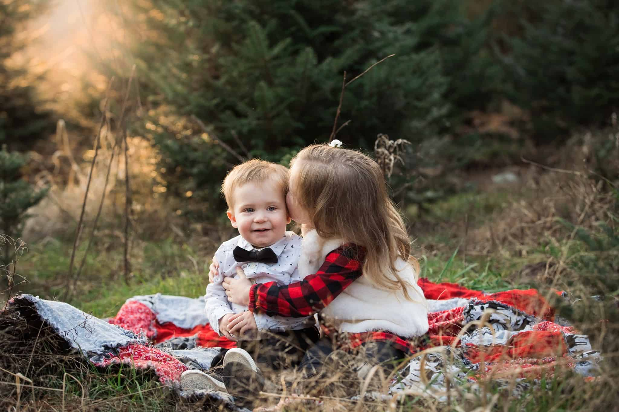 toddler sister kissing baby brother on cheek