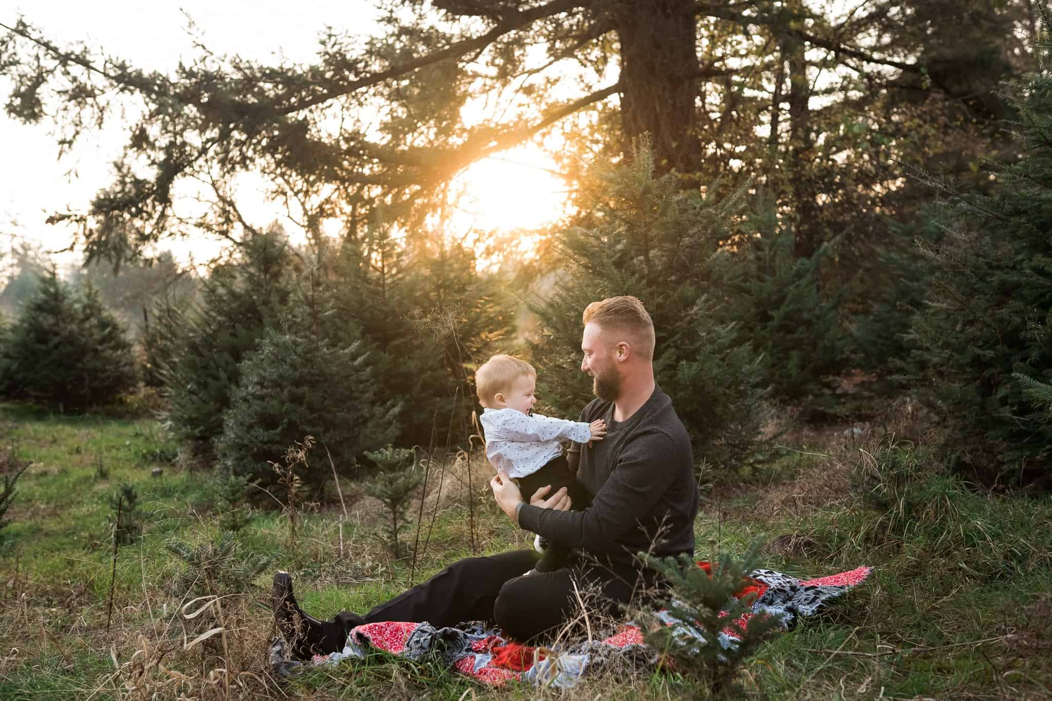 dad holding toddler son on a blanket at sunset