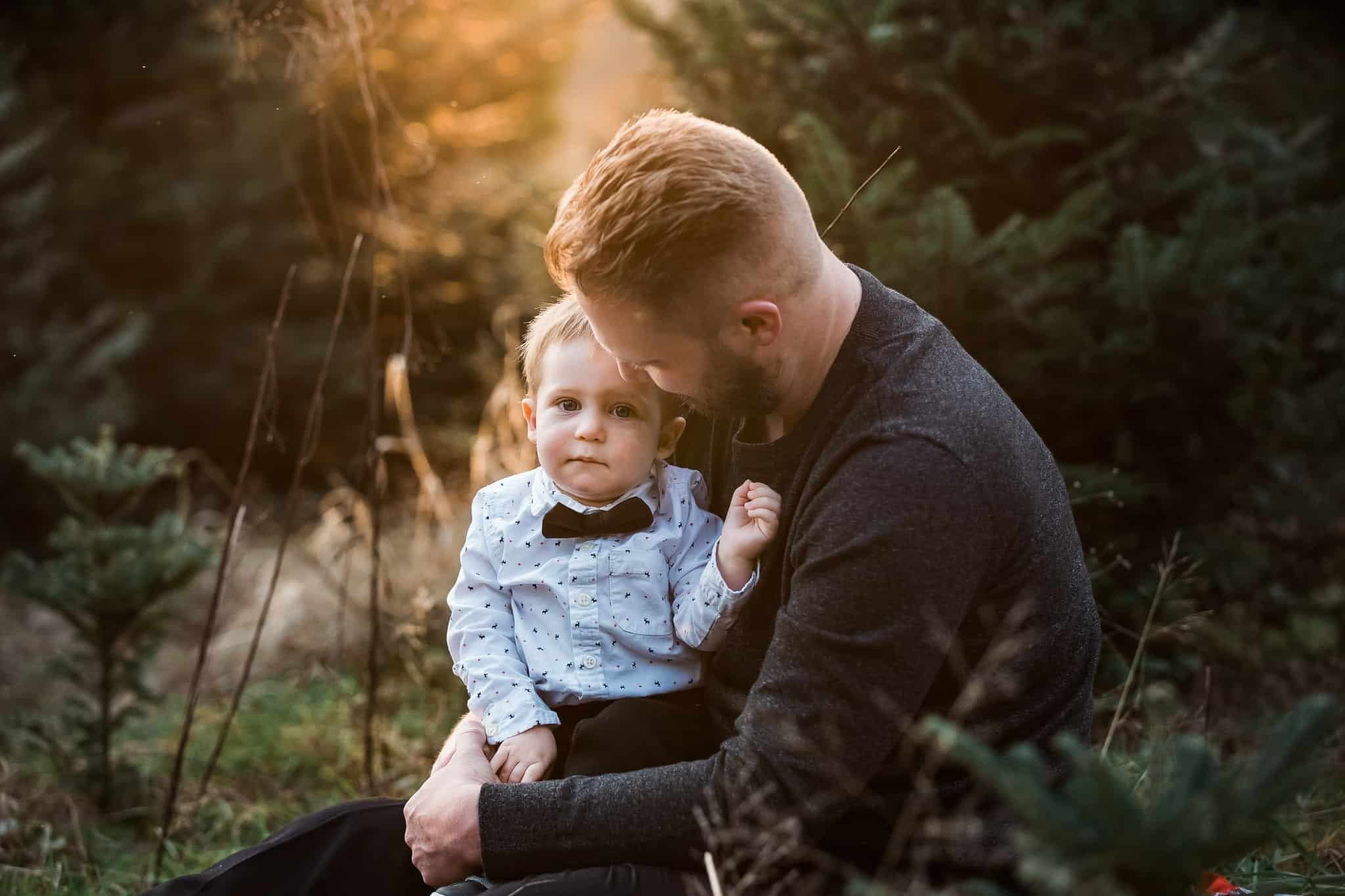 father hugging his son in golden light and evergreen trees