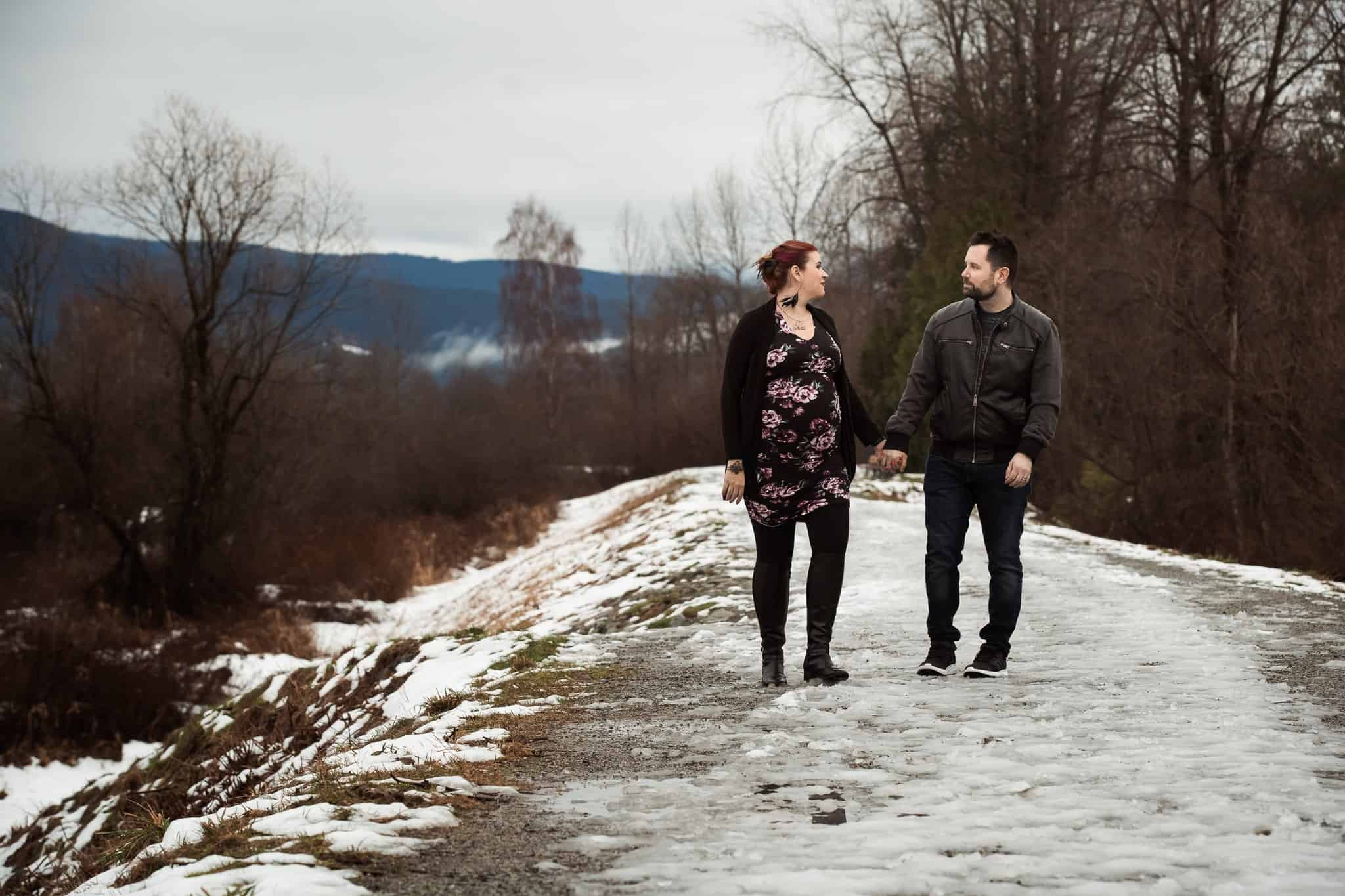 pregnant couple walking along icy winter path holding hands