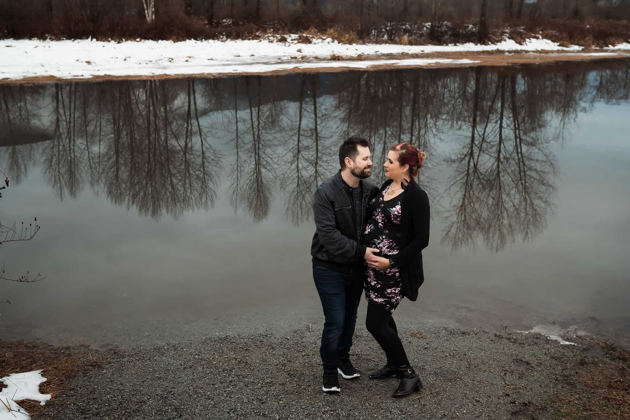 pregnant couple standing by winter river with tree reflections