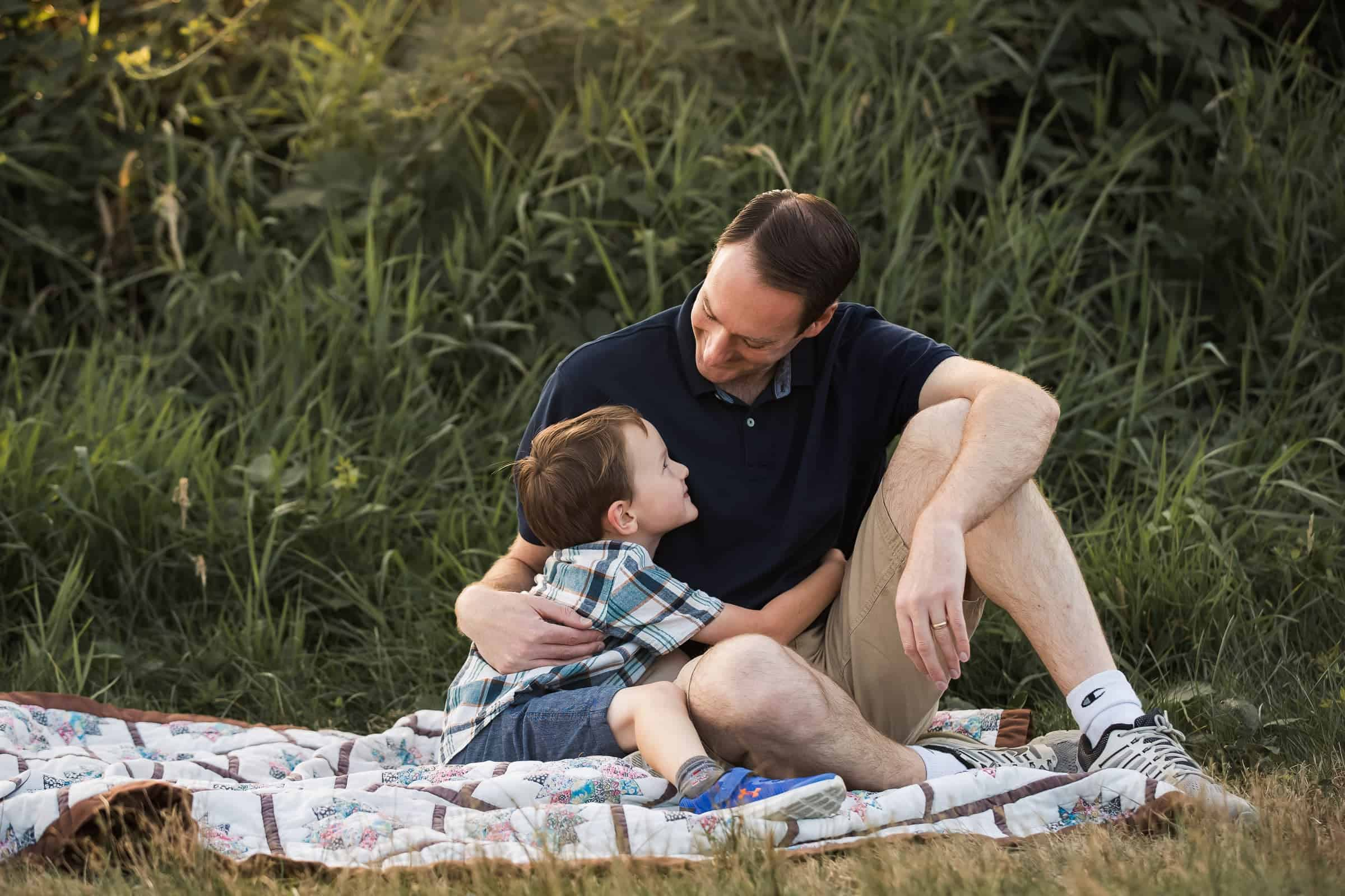 father and son hugging and looking at each other while sitting on a quilt