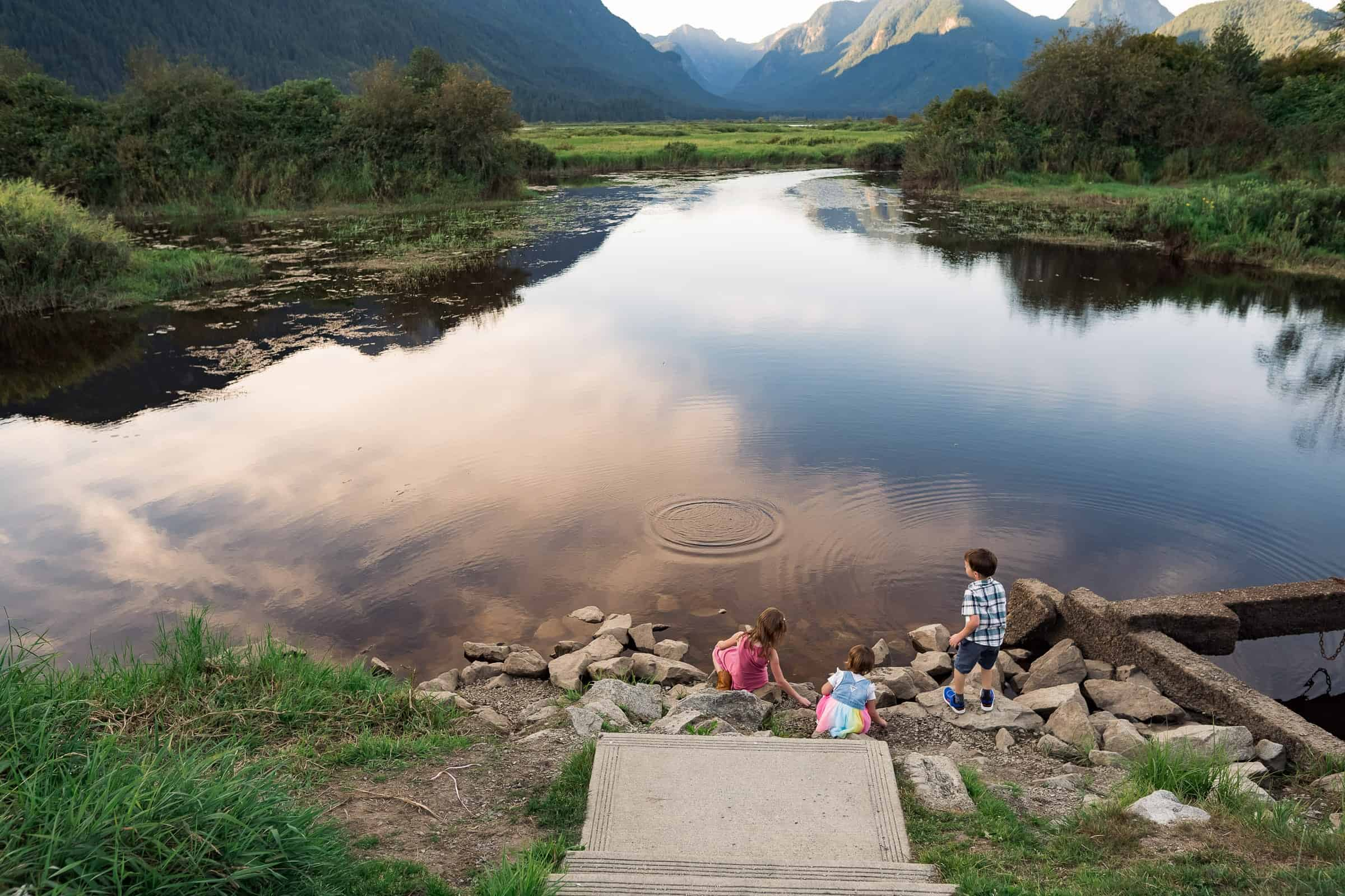 three kids throwing stones in a lake with mountains in the background