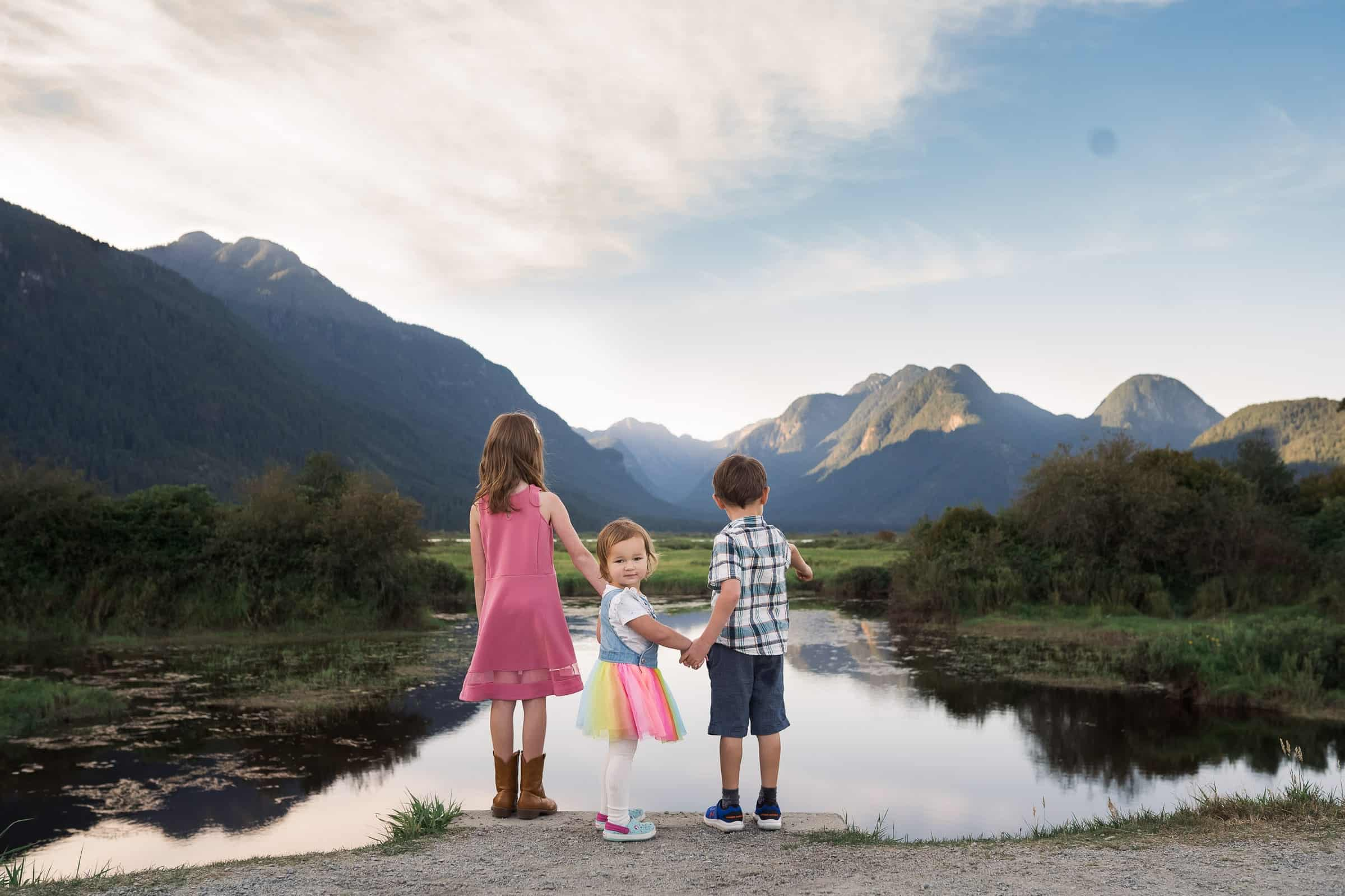 three kids looking out over the lake at the mountains