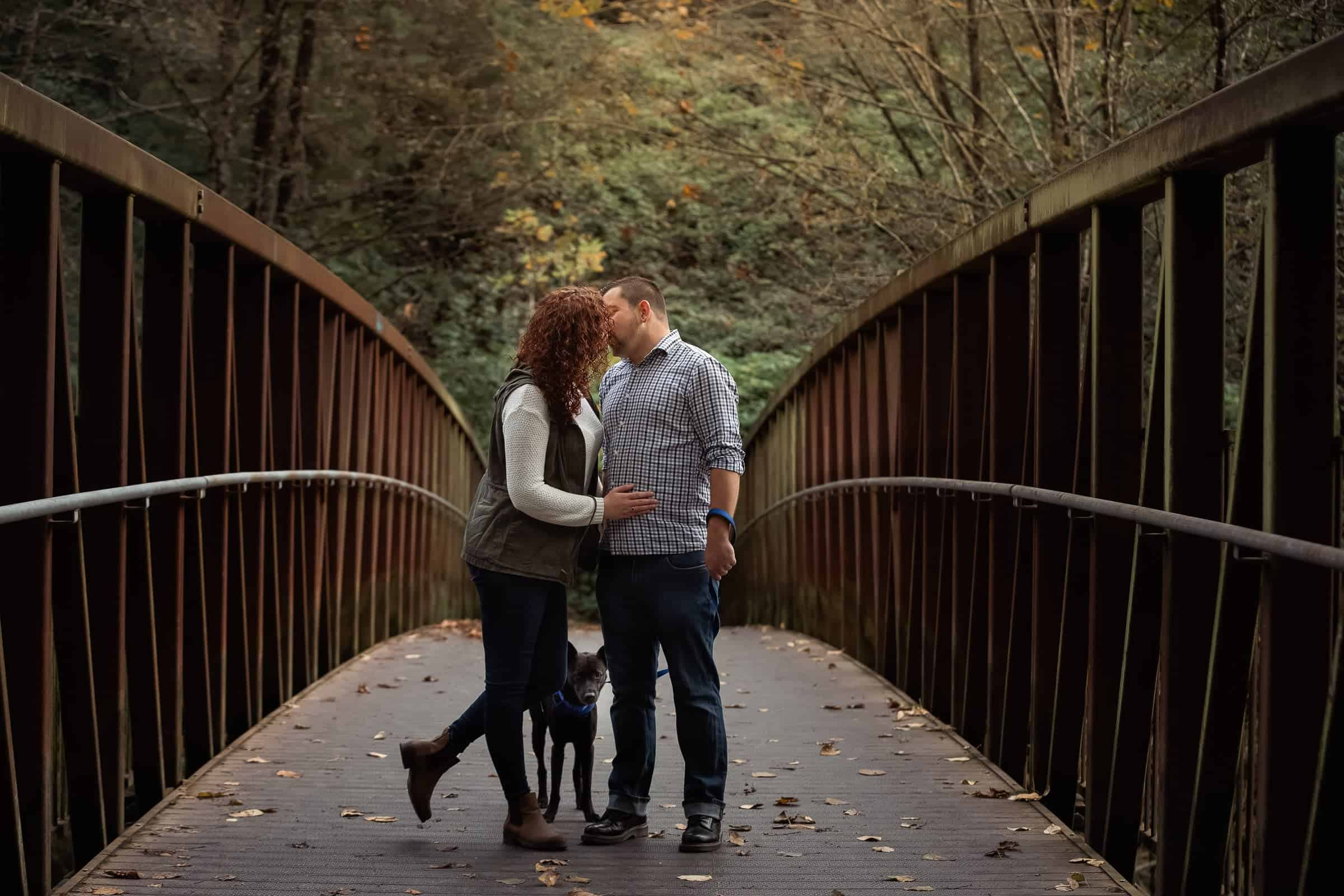 Couple kissing on bridge with dog