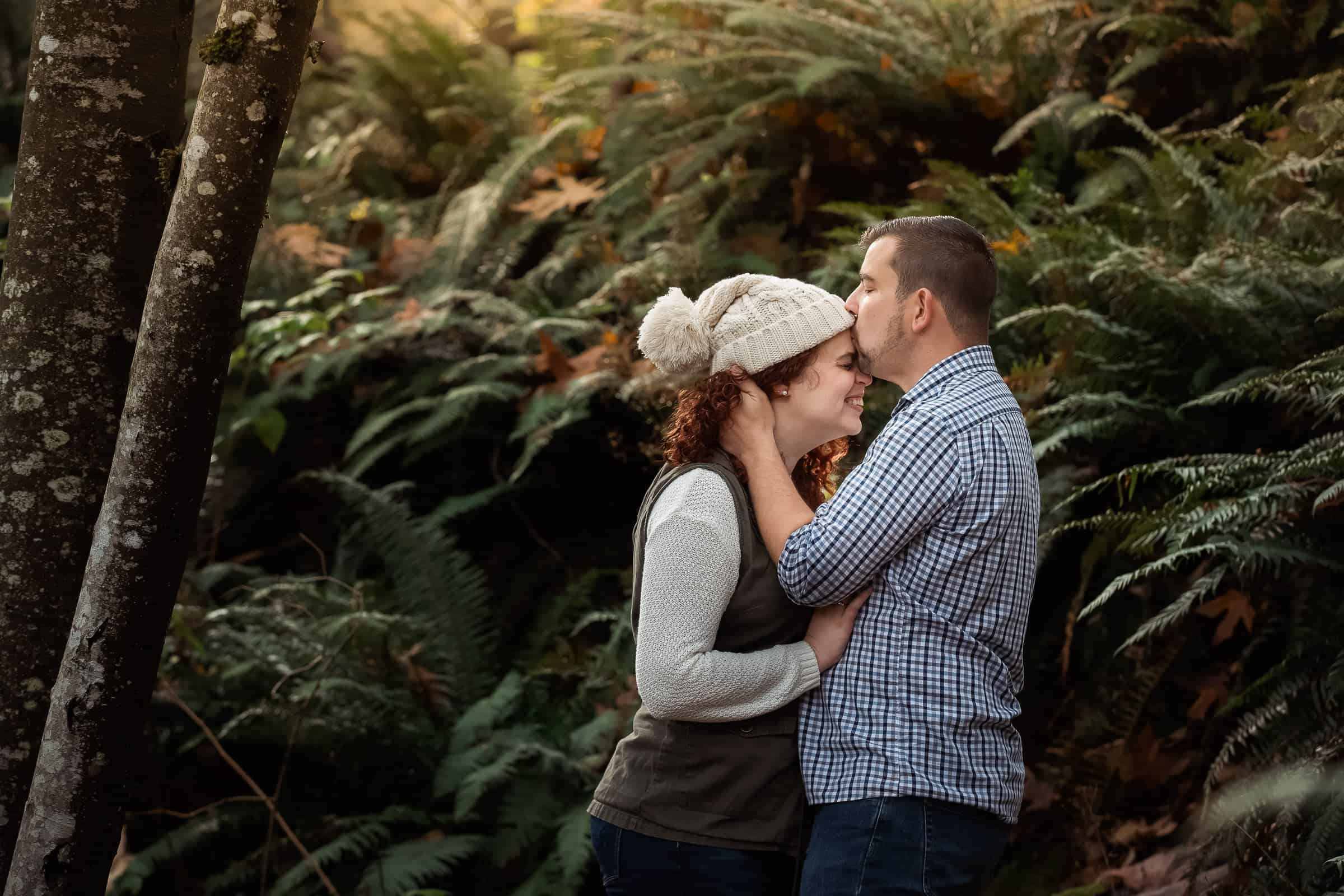 man kissing woman on forehead in rain forest