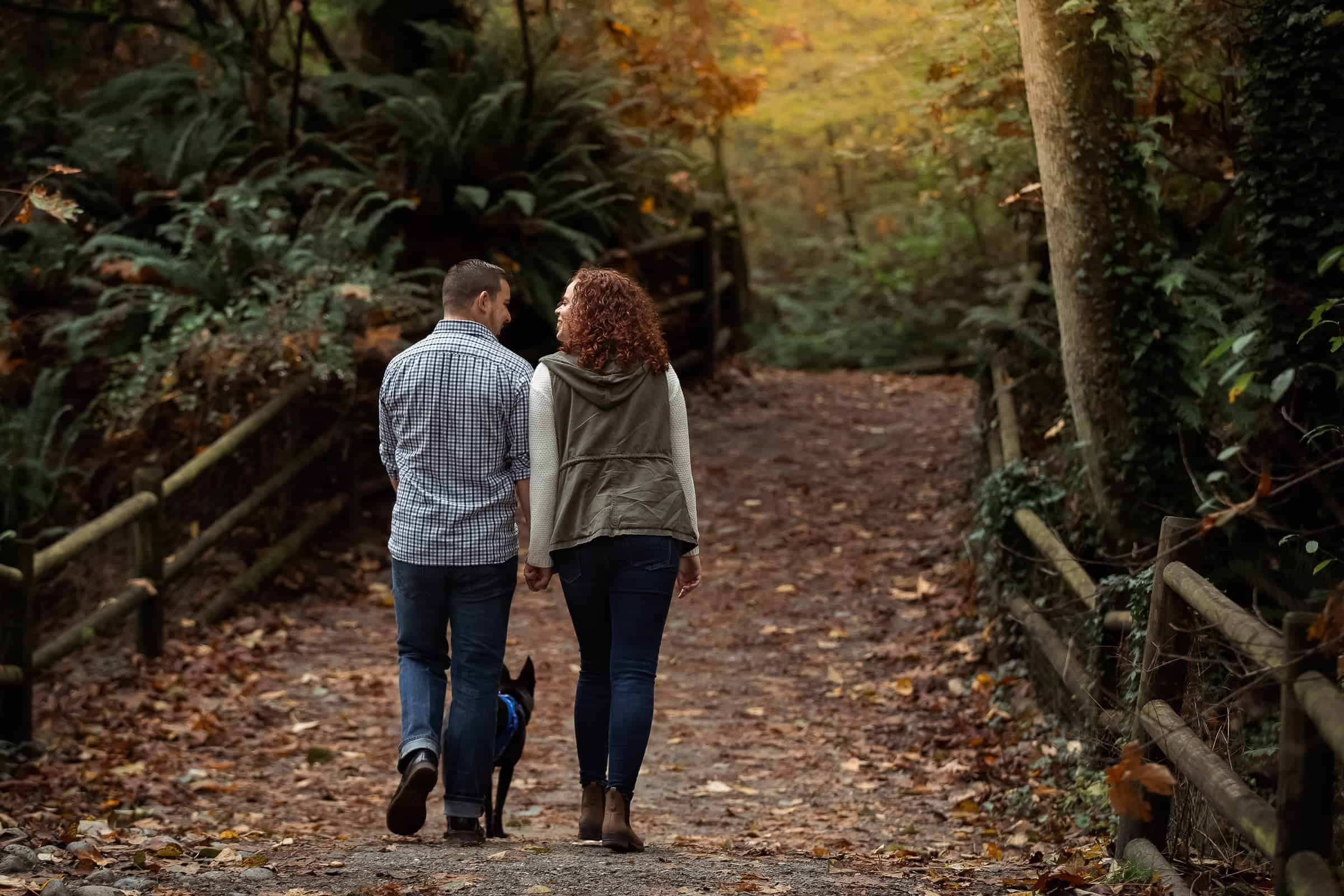 couple walking dog together along a rainforest path