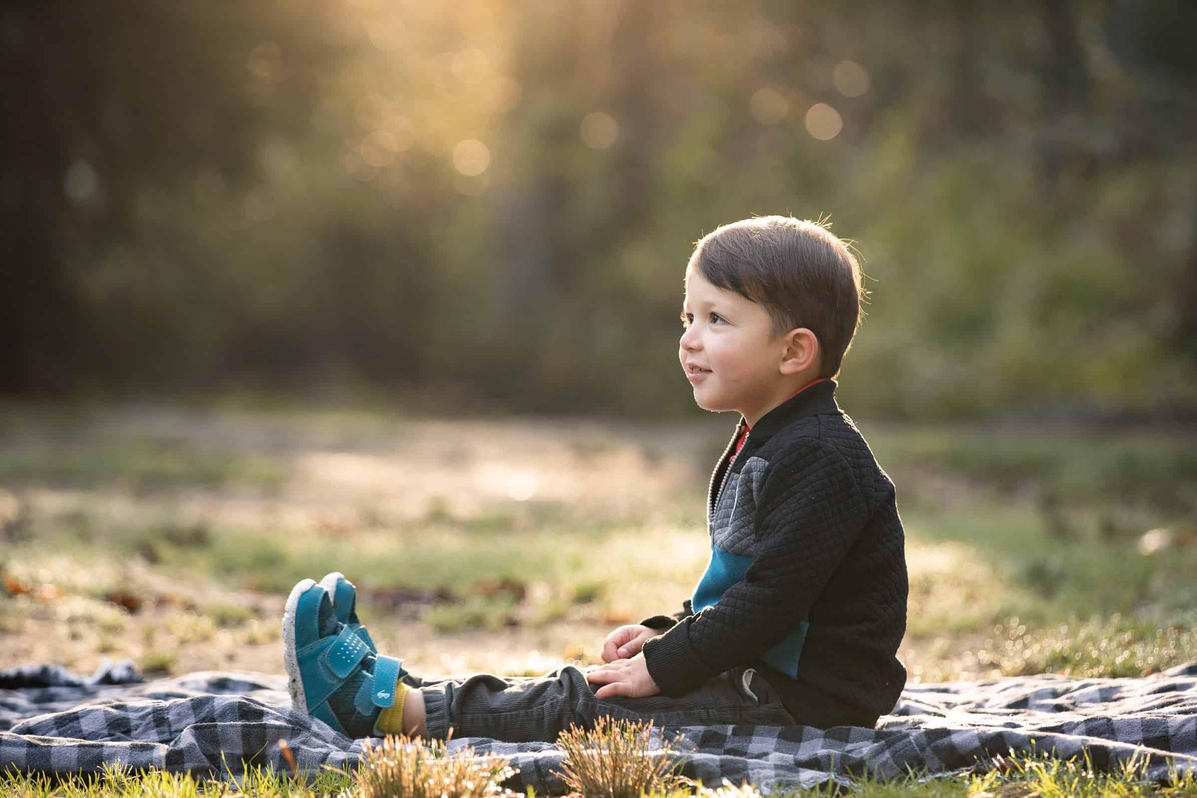 little boy sitting on blanket looking up
