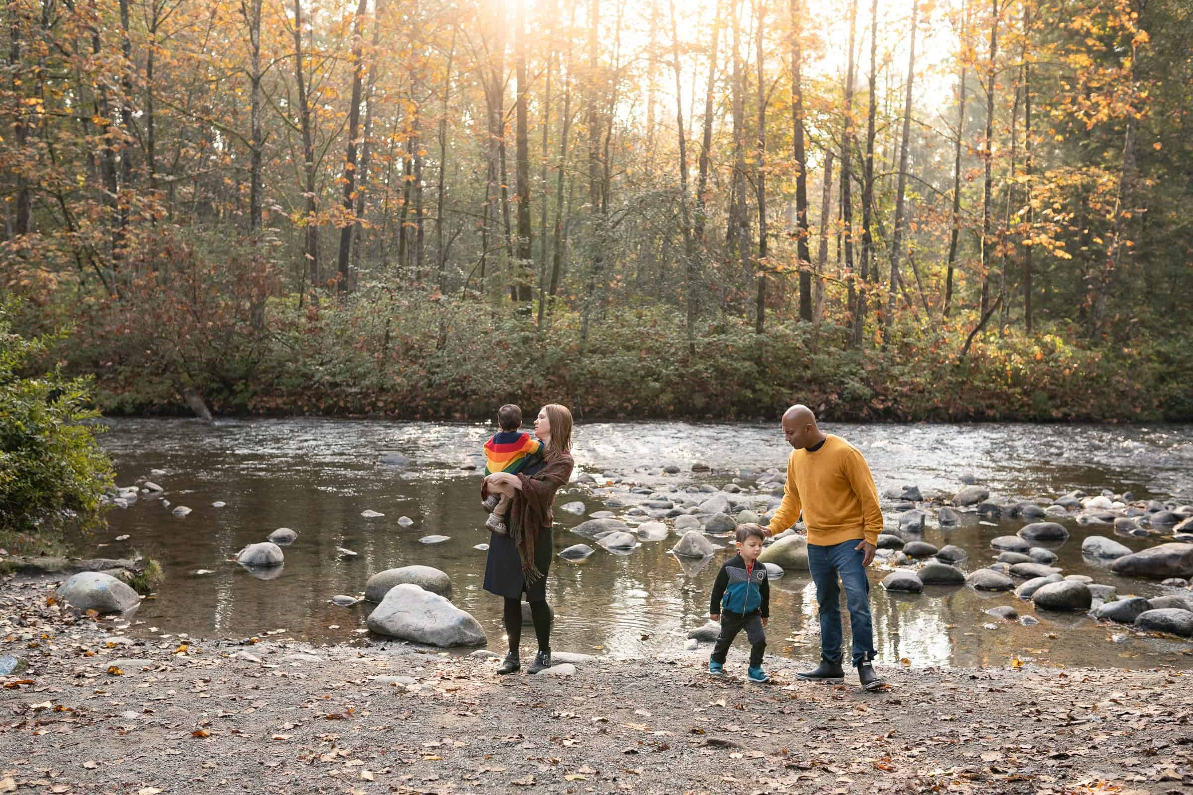 family playing by fall riverbank