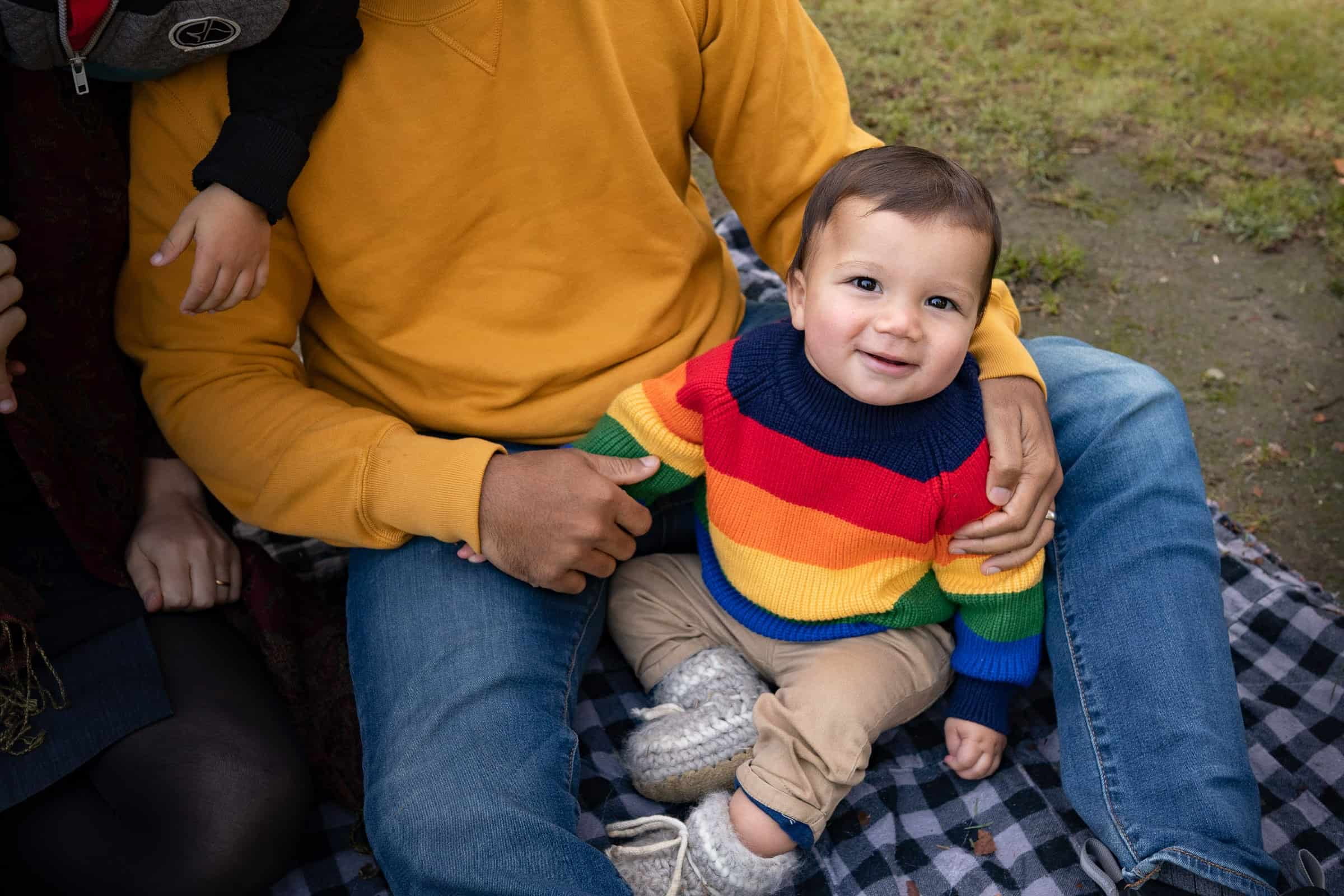 little boy in rainbow sweater being held in father's lap