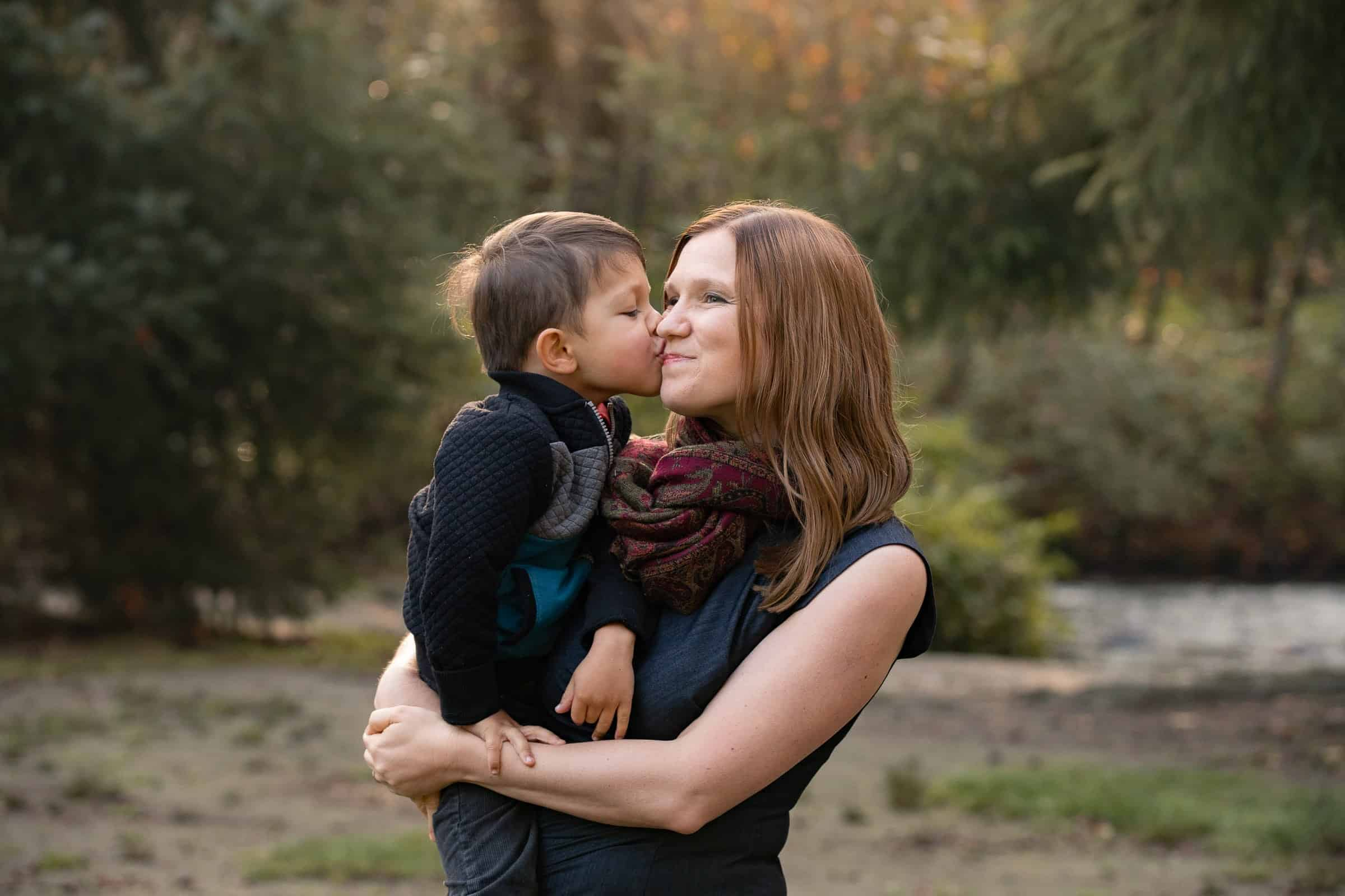 mother holding toddler son in her arms while he kisses her cheek