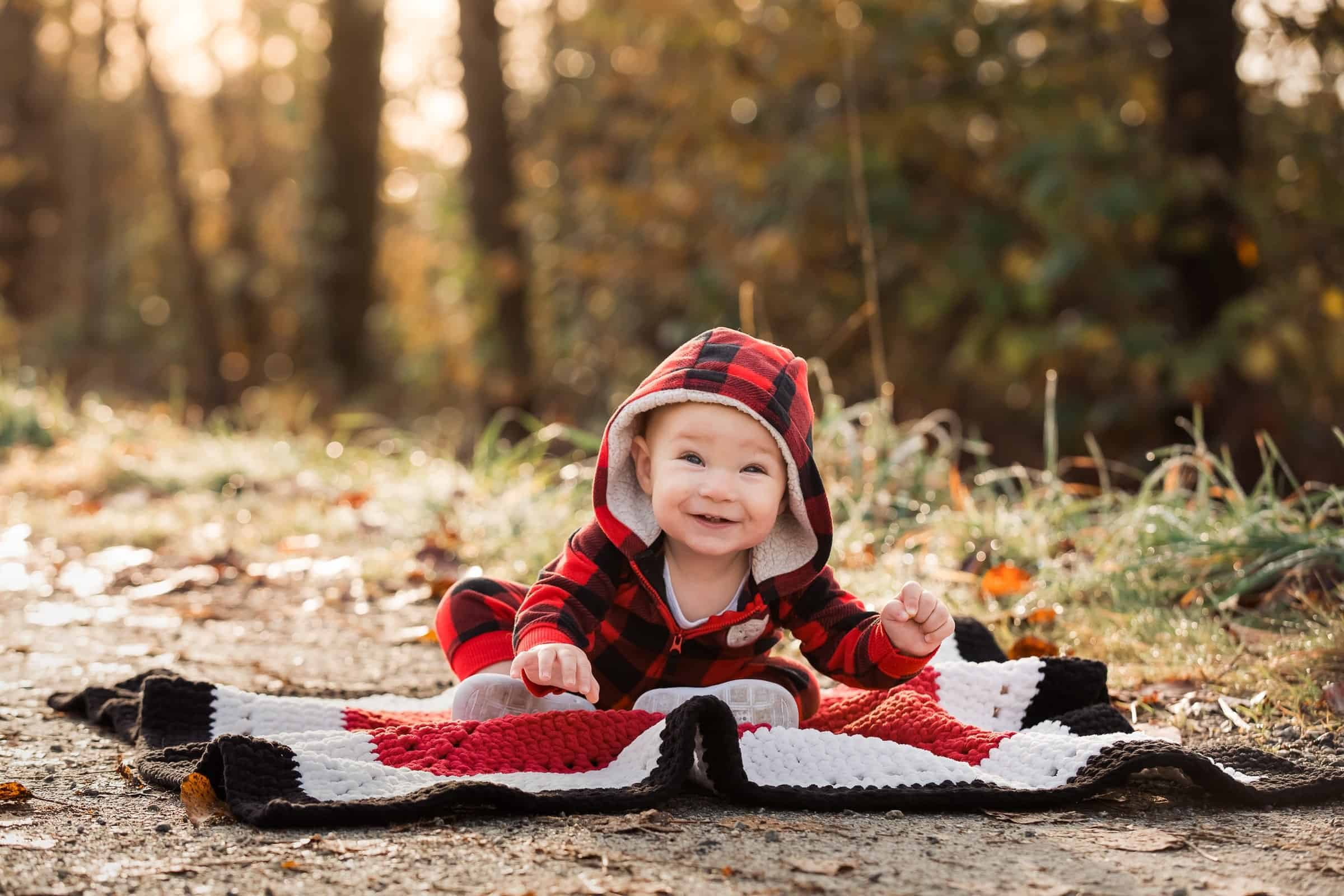 smiling baby laying on blanket outside