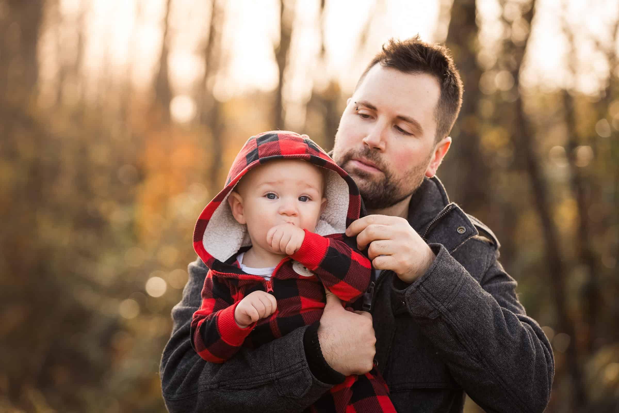 dad holding baby adjusting hood