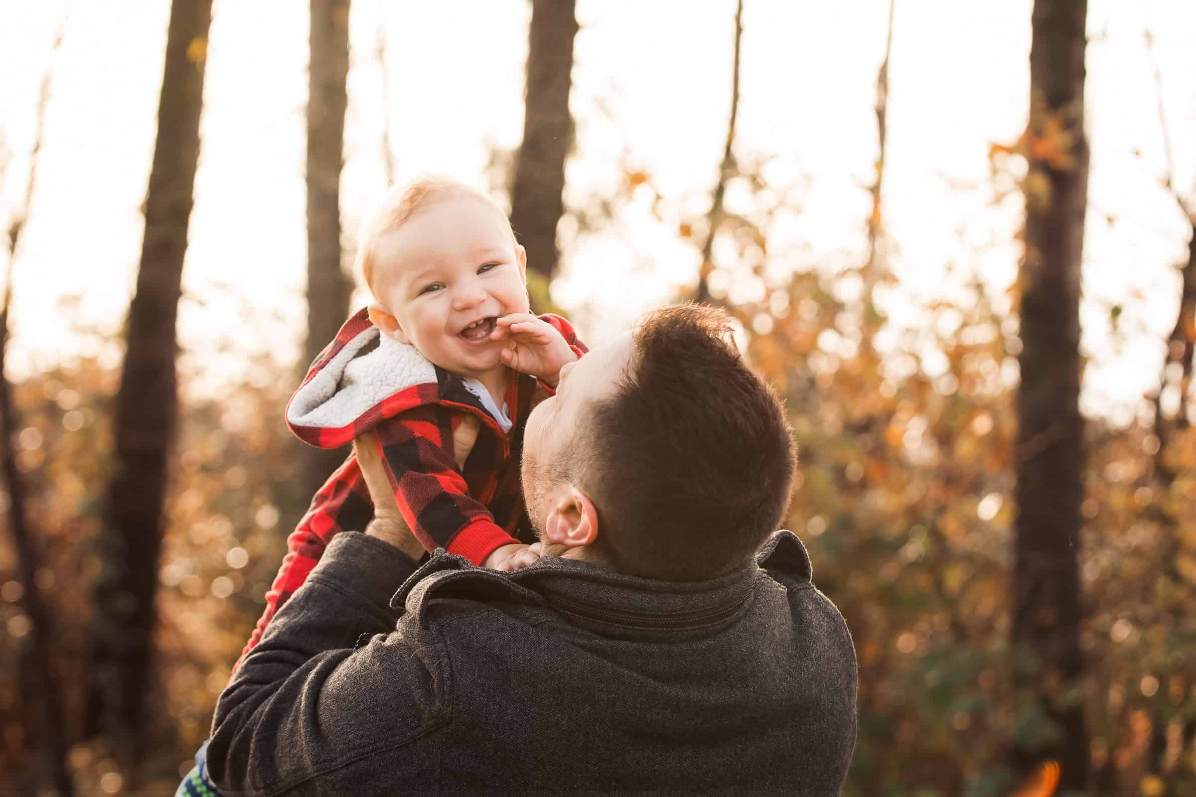 dad holding laughing baby in the air