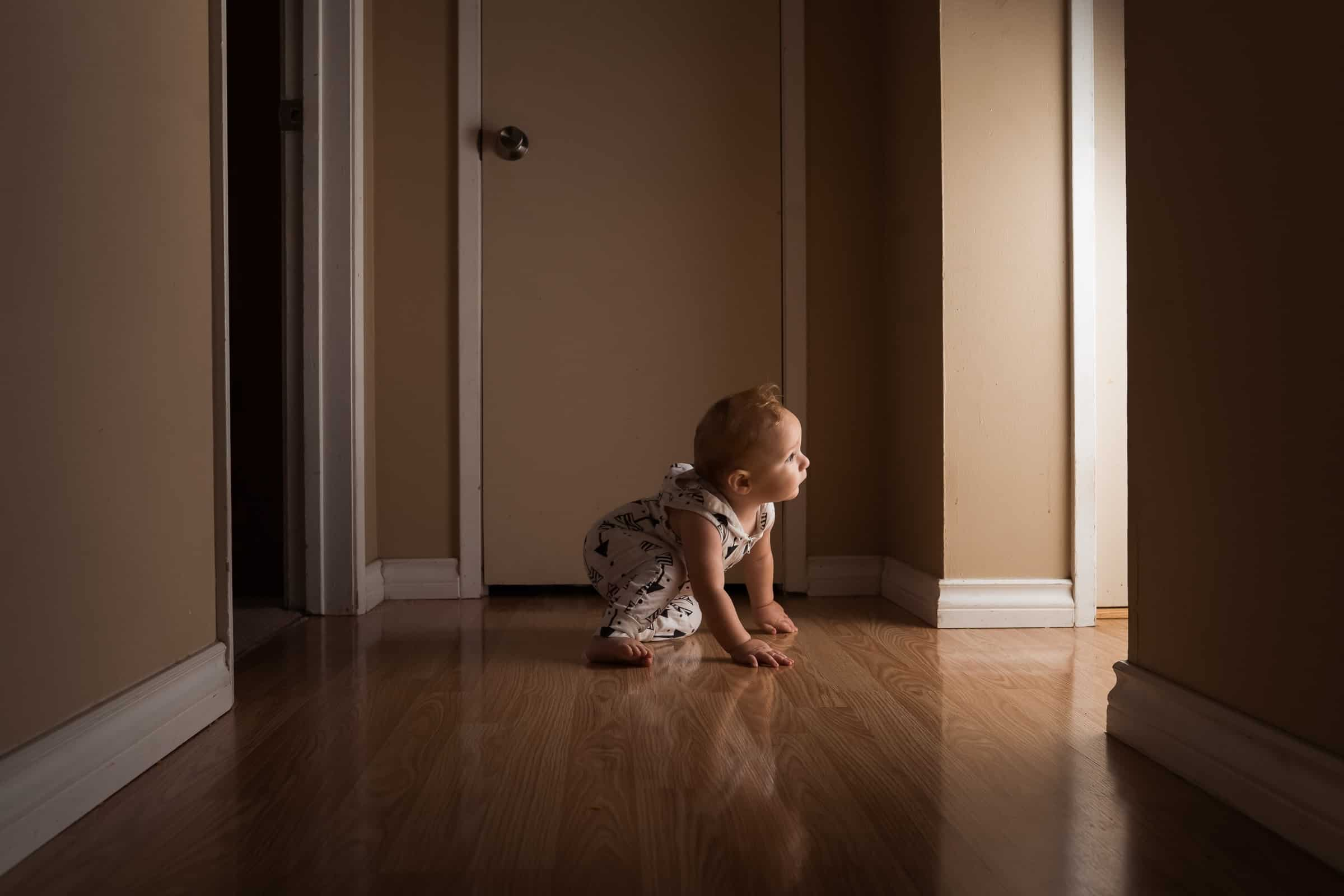 little boy crawling in dark hallway looking toward the light