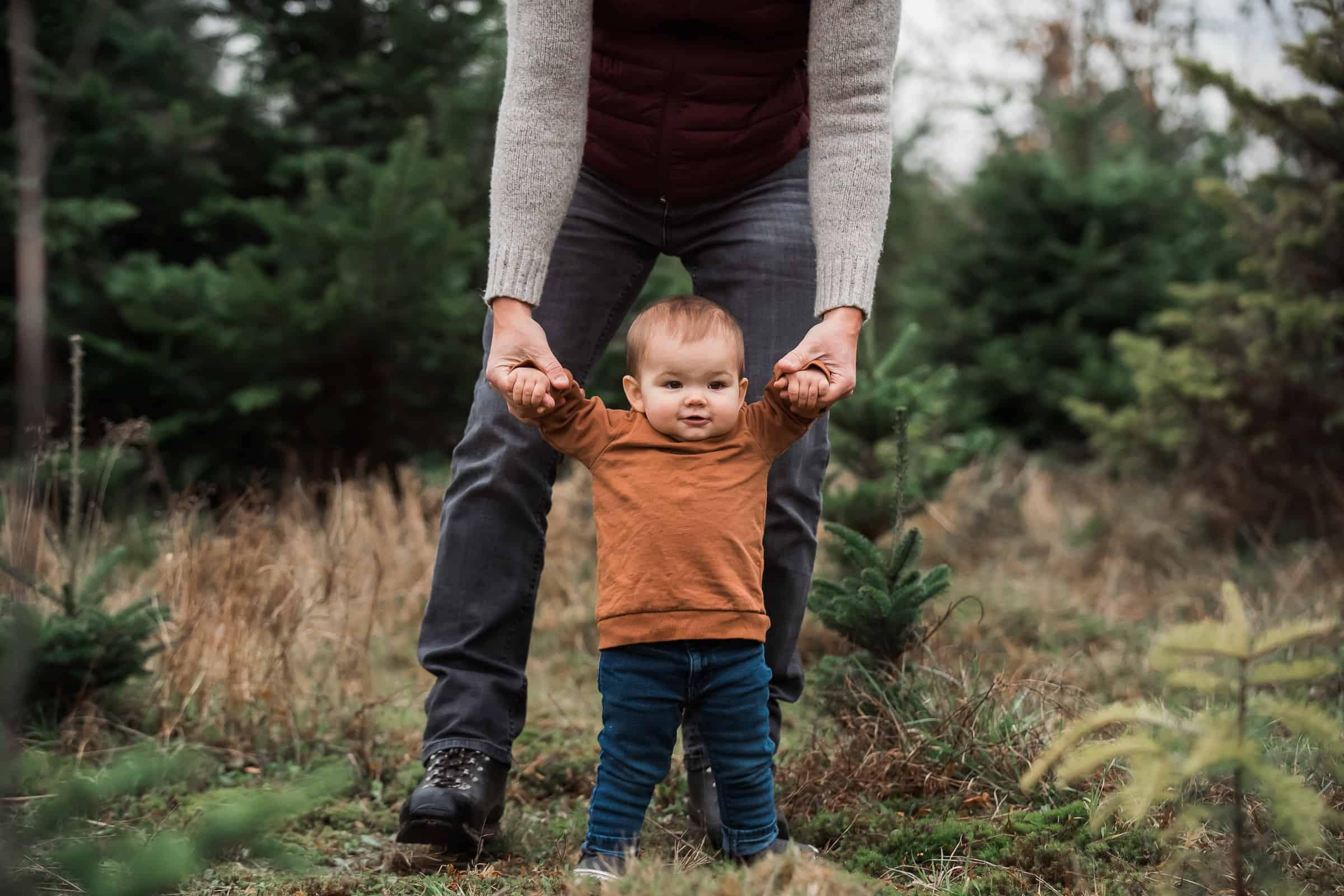 father holding daughter's hands as she learns to walk