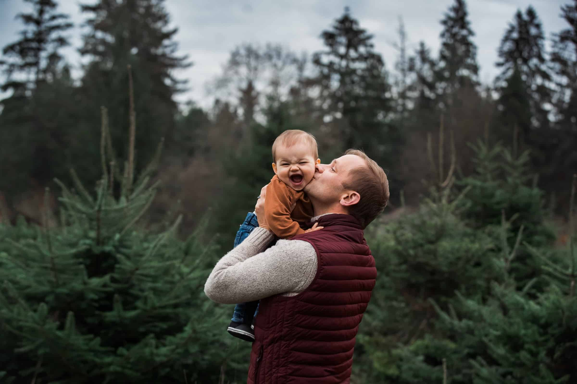 father kissing laughing baby's cheek in evergreen forest