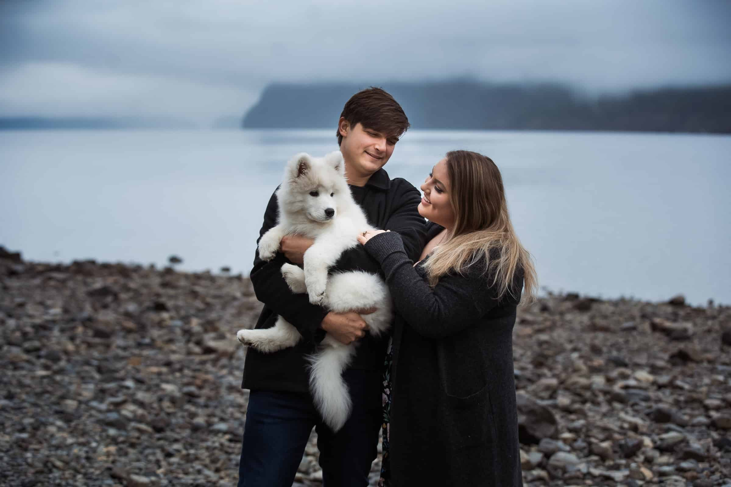 couple holding white fluffy dog by foggy lake