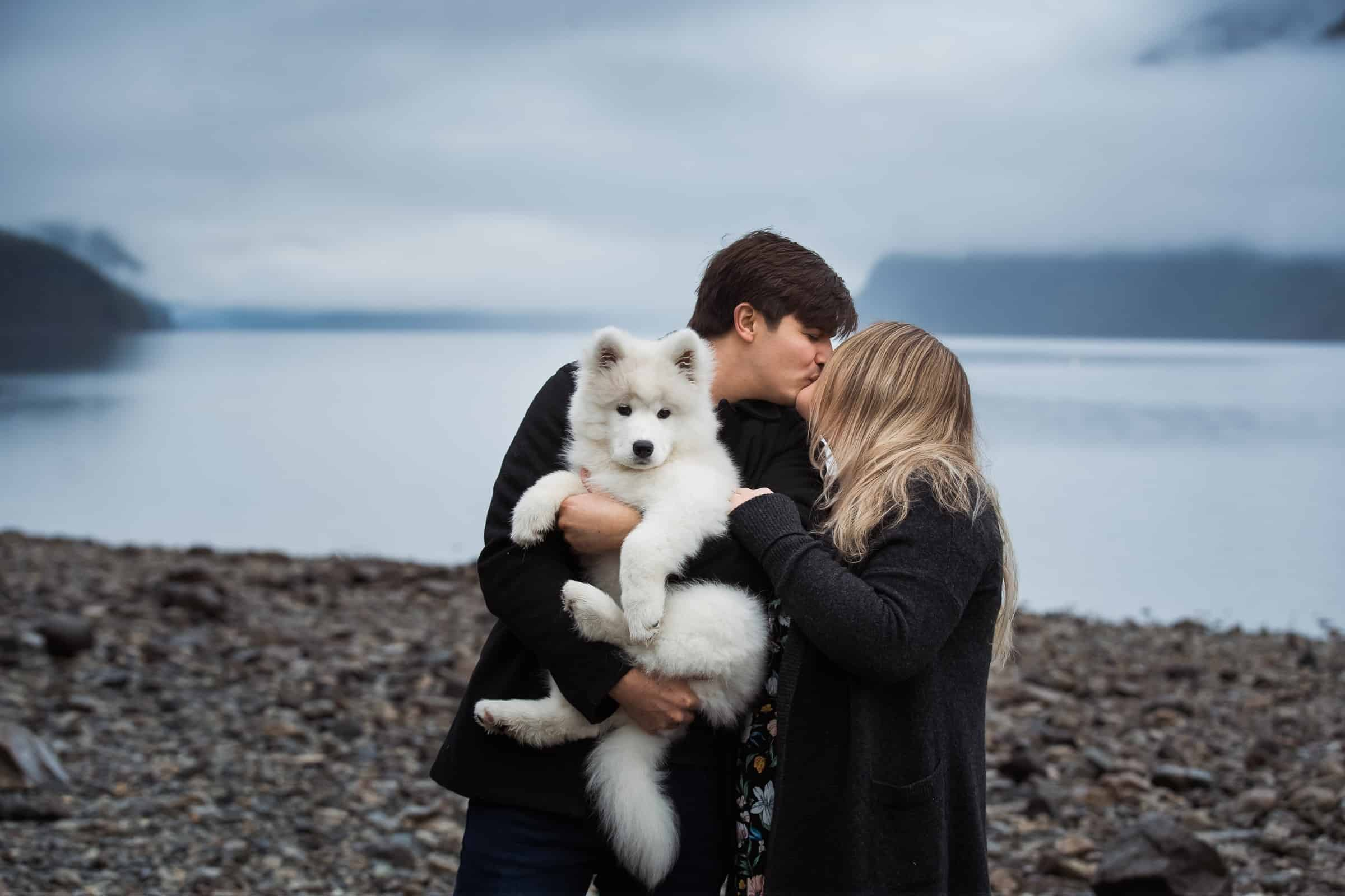 couple kissing by foggy lake with white fluffy dog