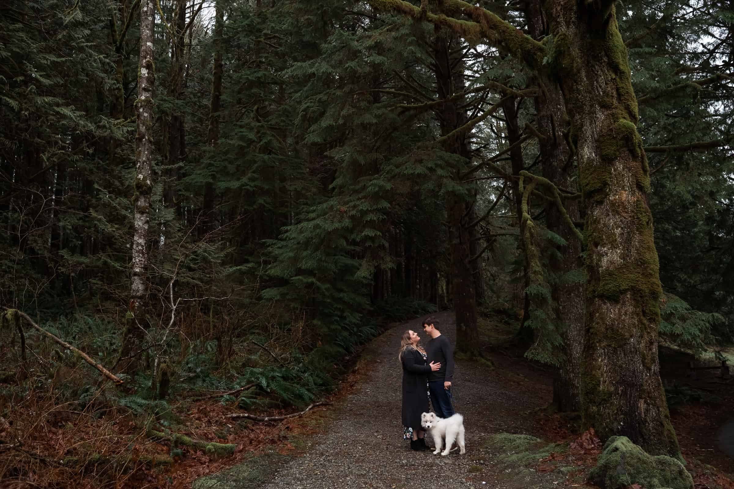 couple on forest path with white fluffy dog