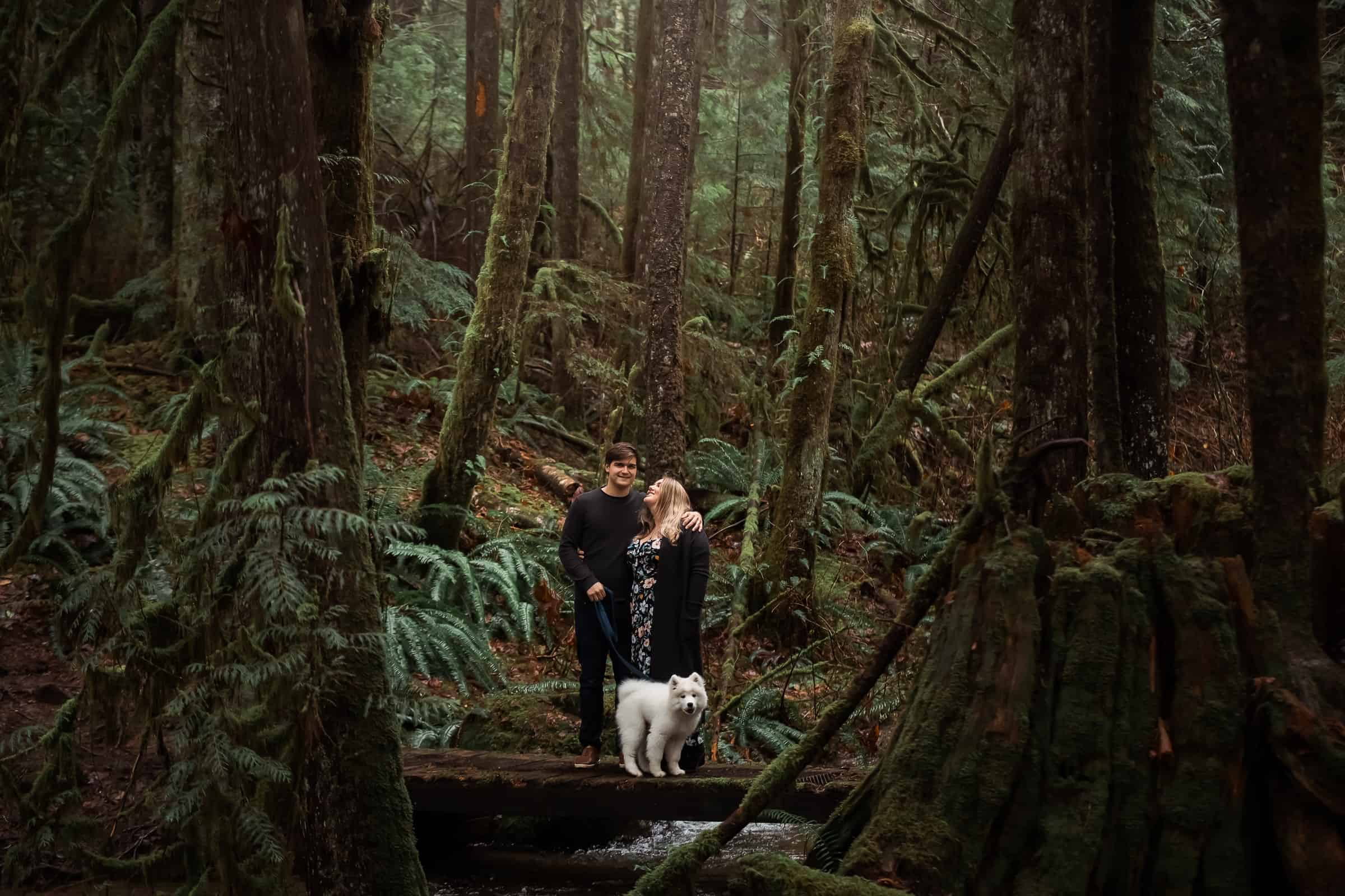 Couple in rain forest with white fluffy dog