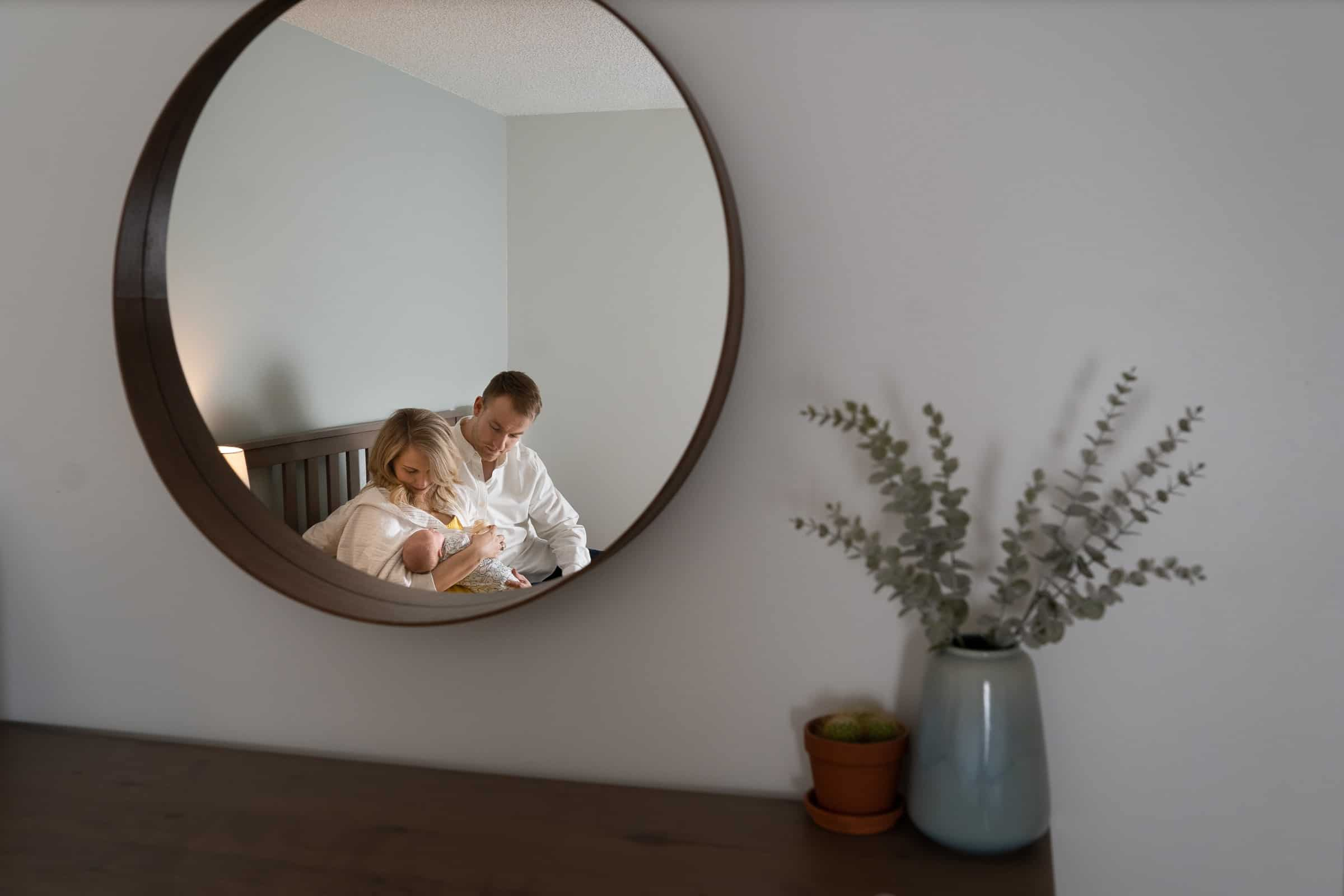 reflection of parents in mirror holding newborn