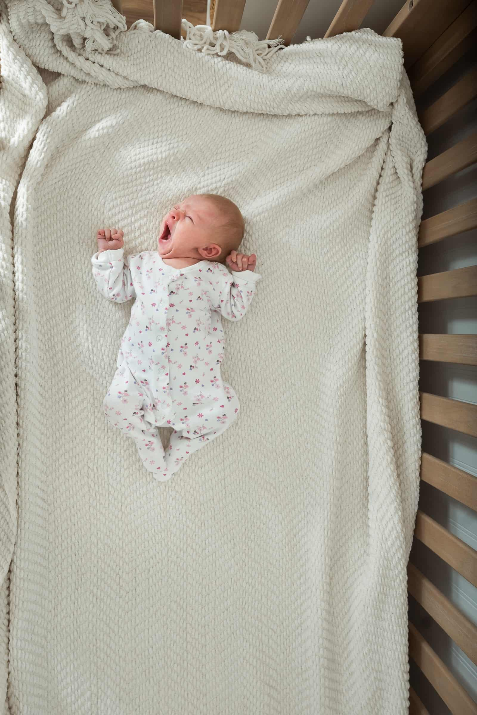 baby laying in crib yawning