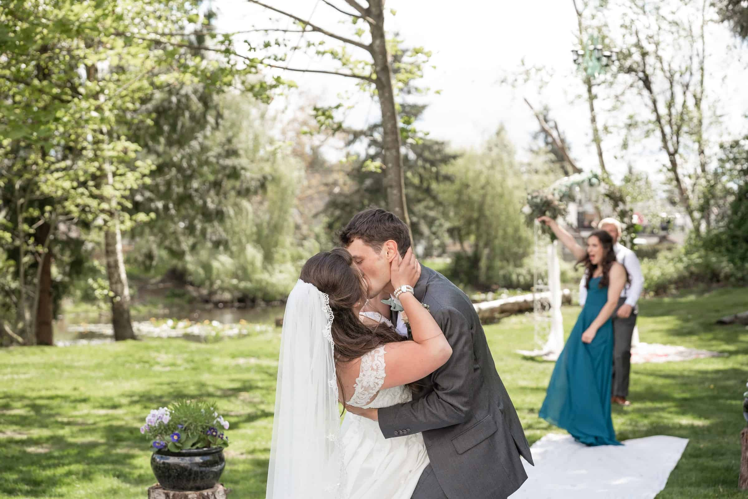 bride and groom kissing with people celebrating in background