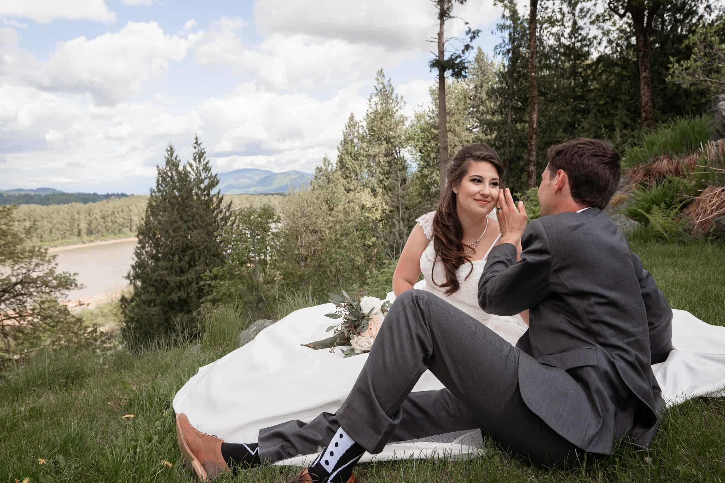bride and groom sitting on cliff with river and mountains behind them