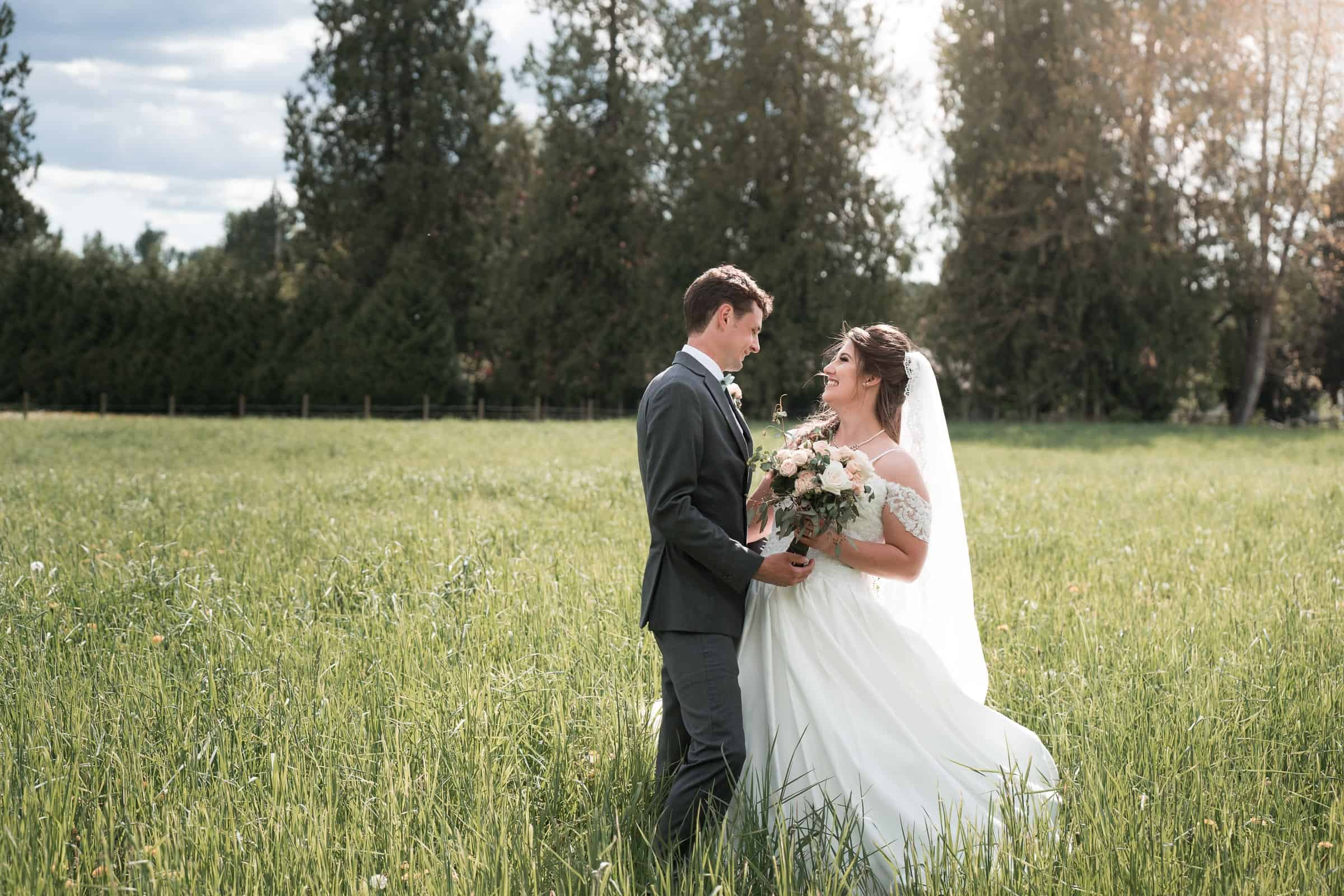 bride and groom in large hay field at sunset