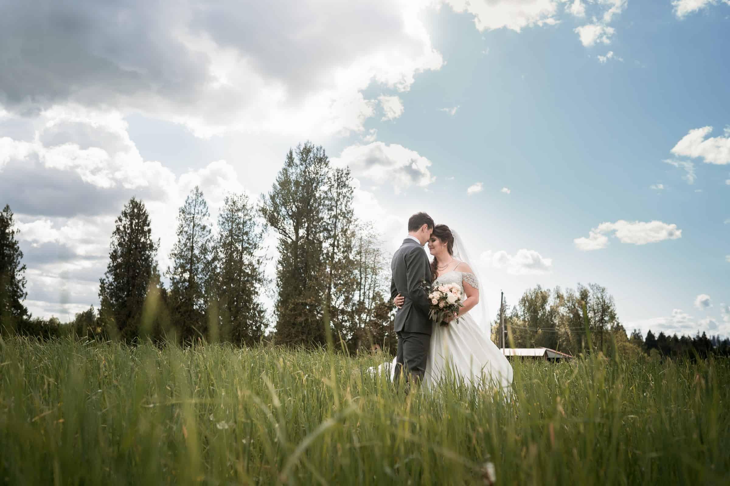 bride and groom in large hay field