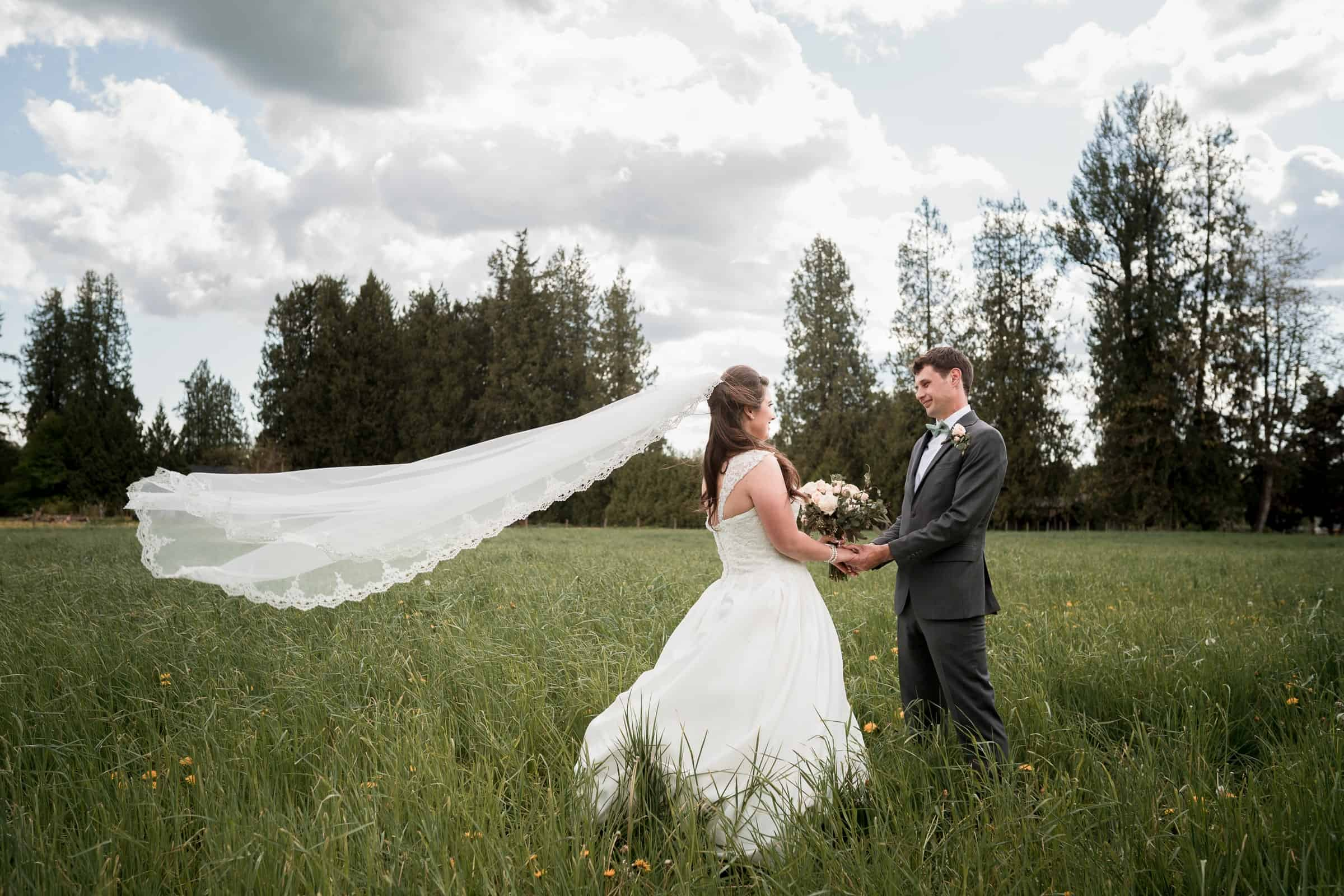 bride and groom in field with wind blowing veil