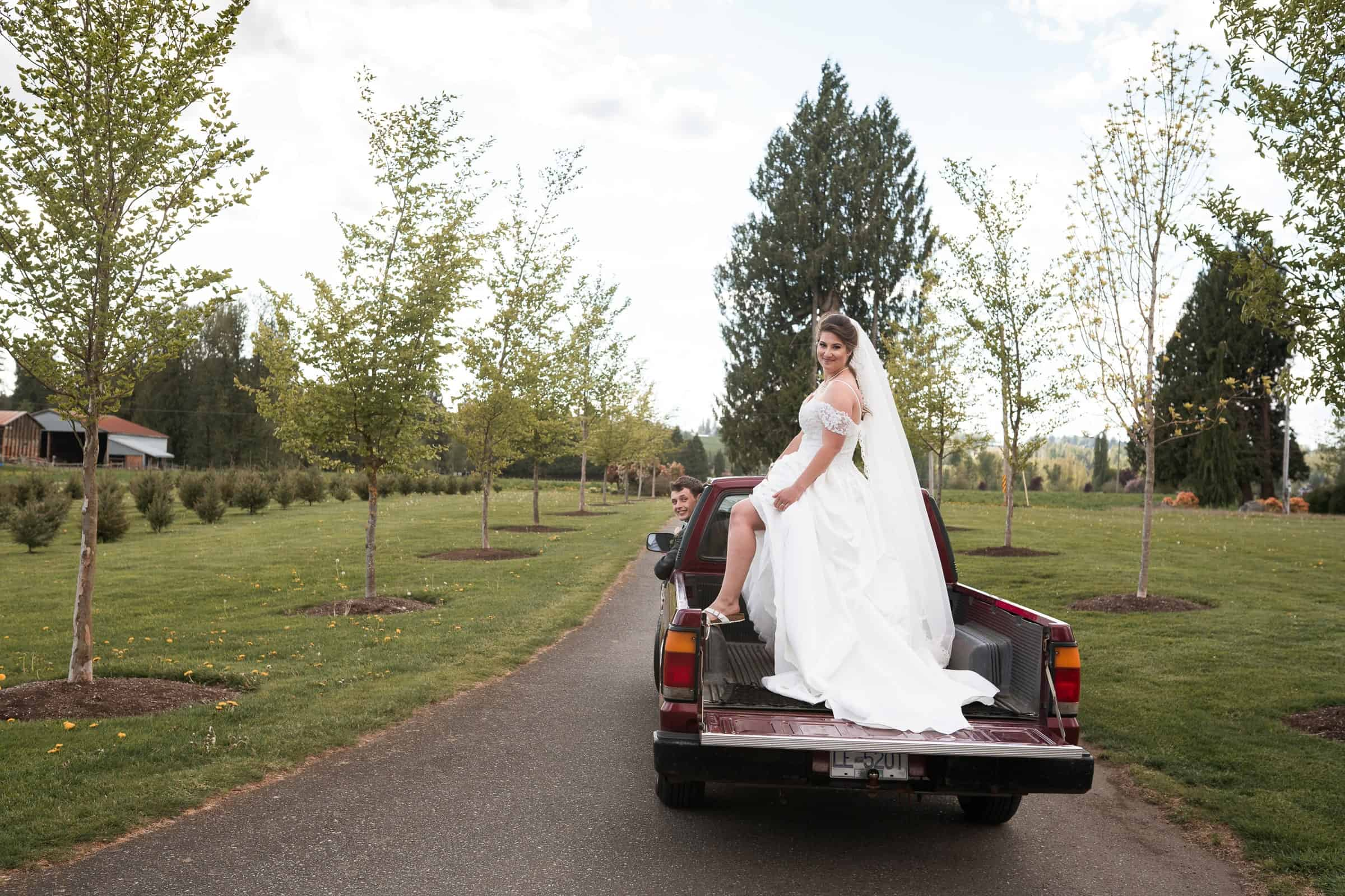 bride posing in back of pick up truck
