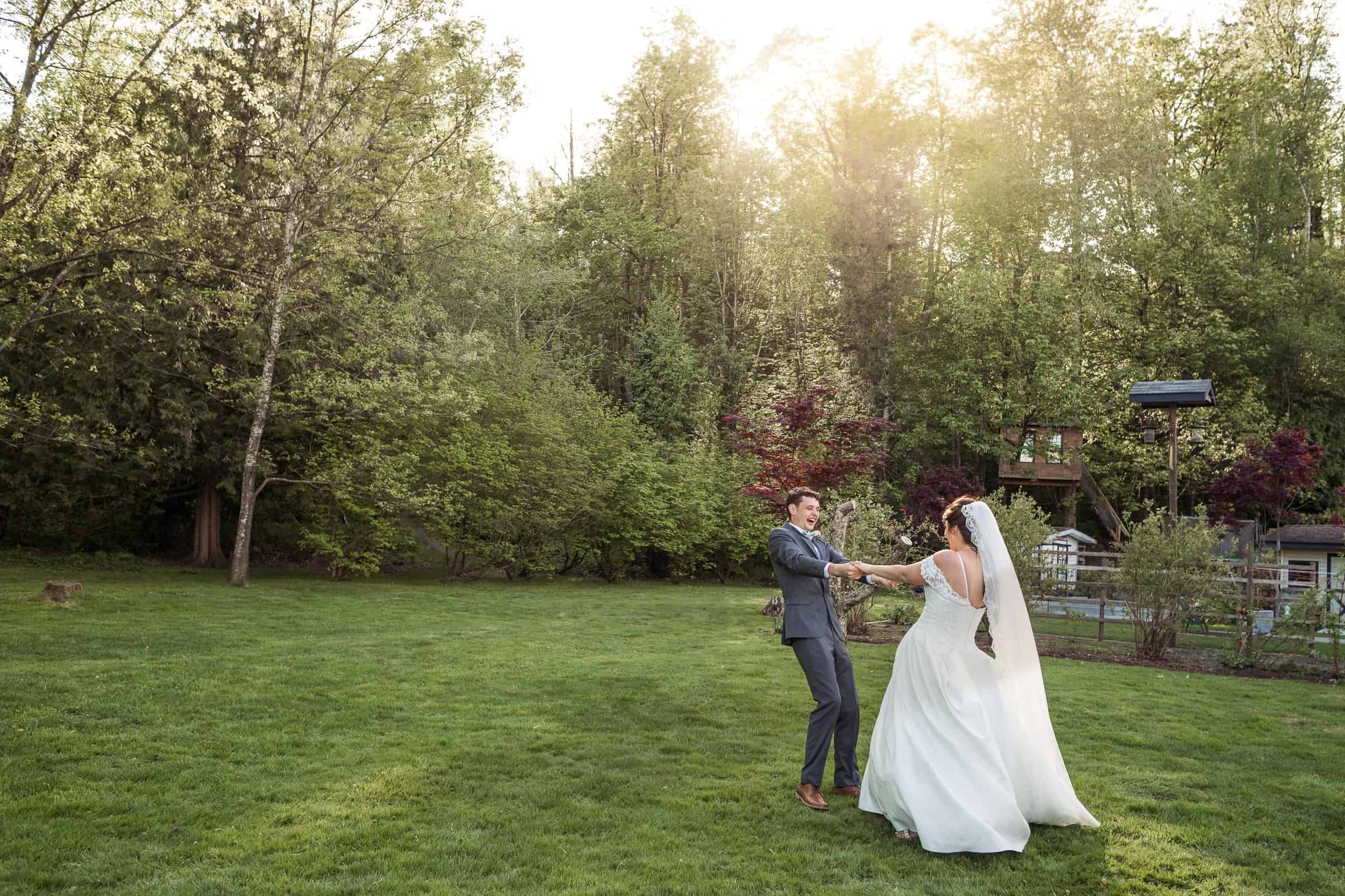bride and groom dancing in large backyard at sunset