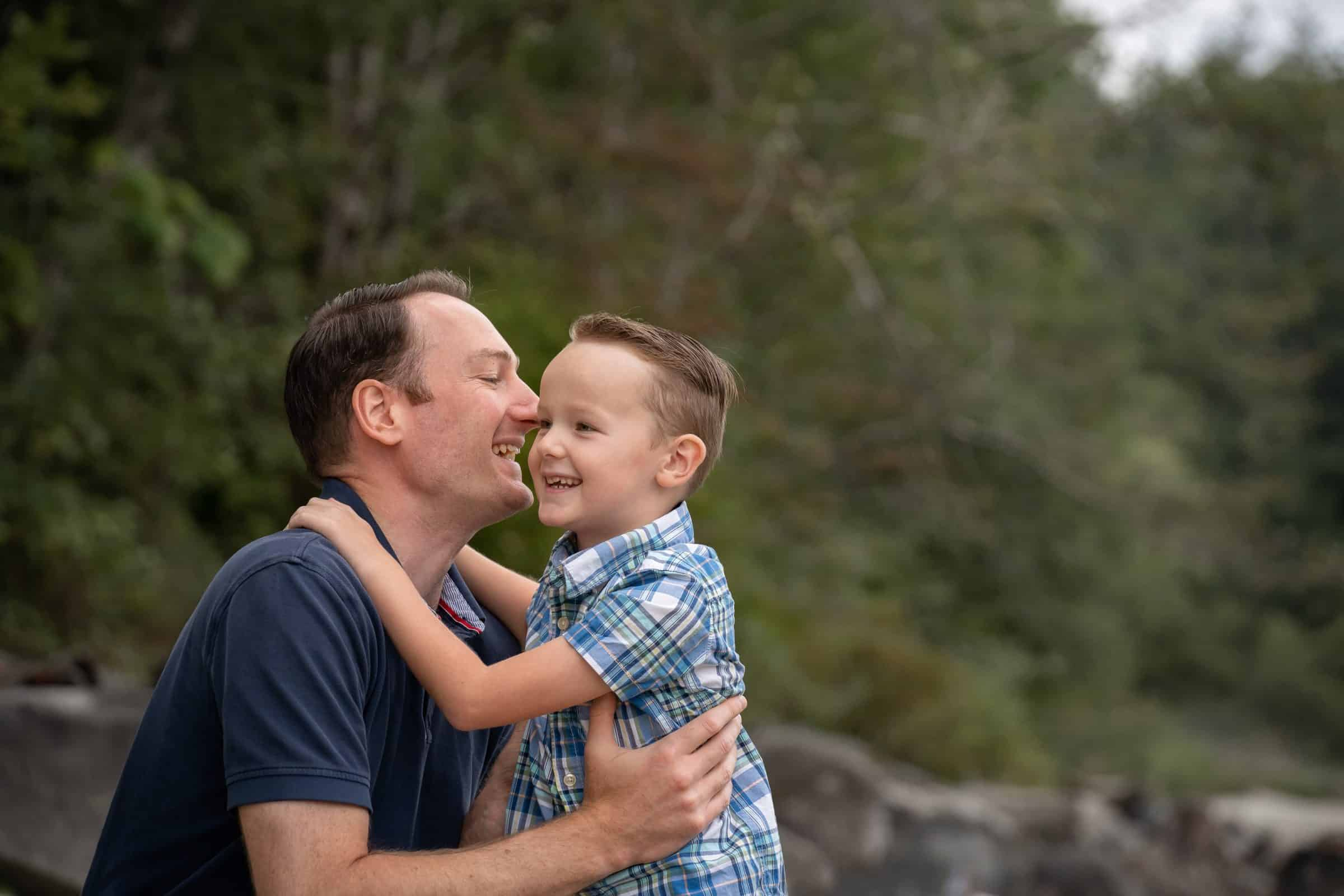 close up of father holding son and laughing