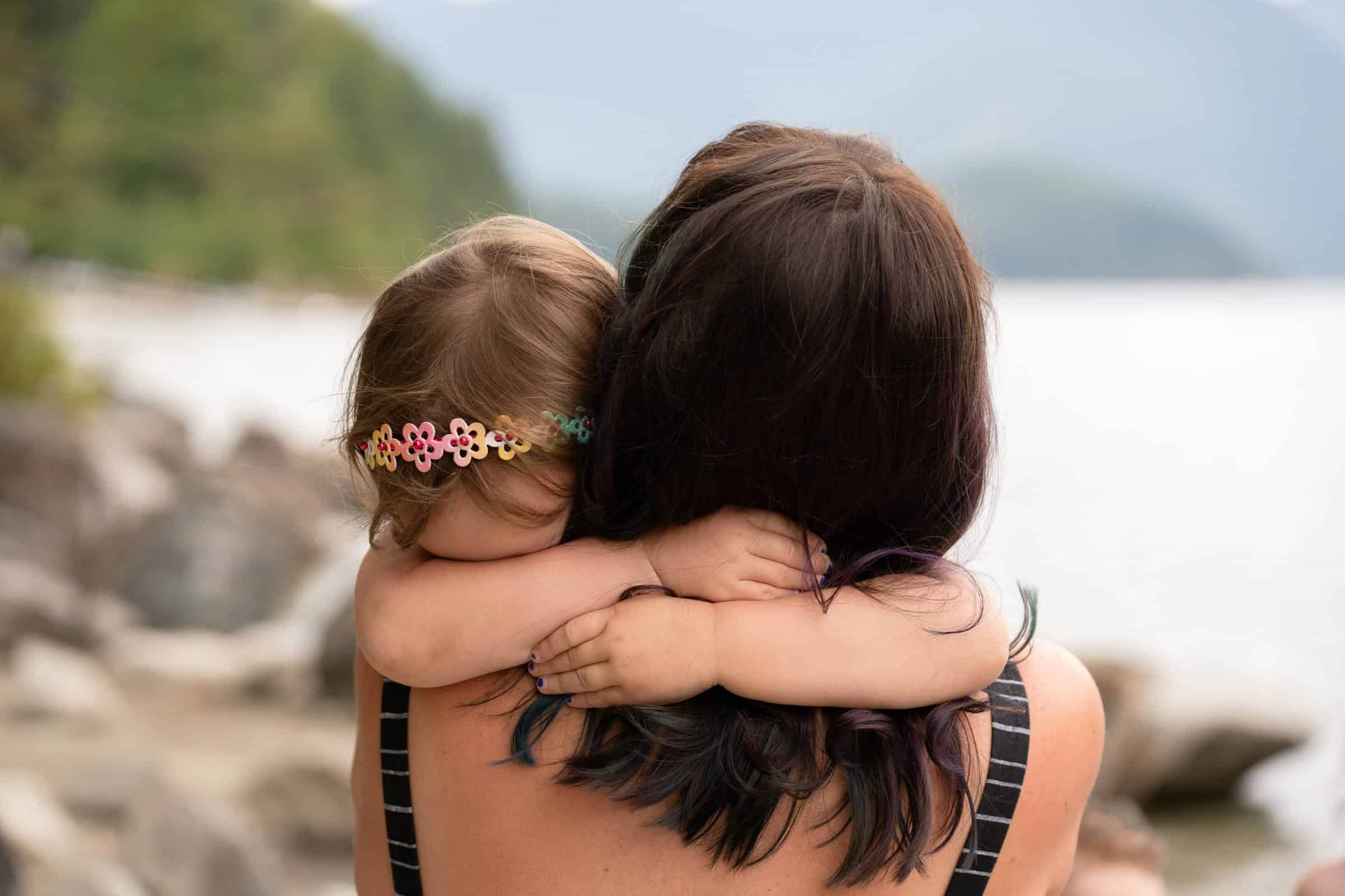 little girl wrapping her arms around mom's neck