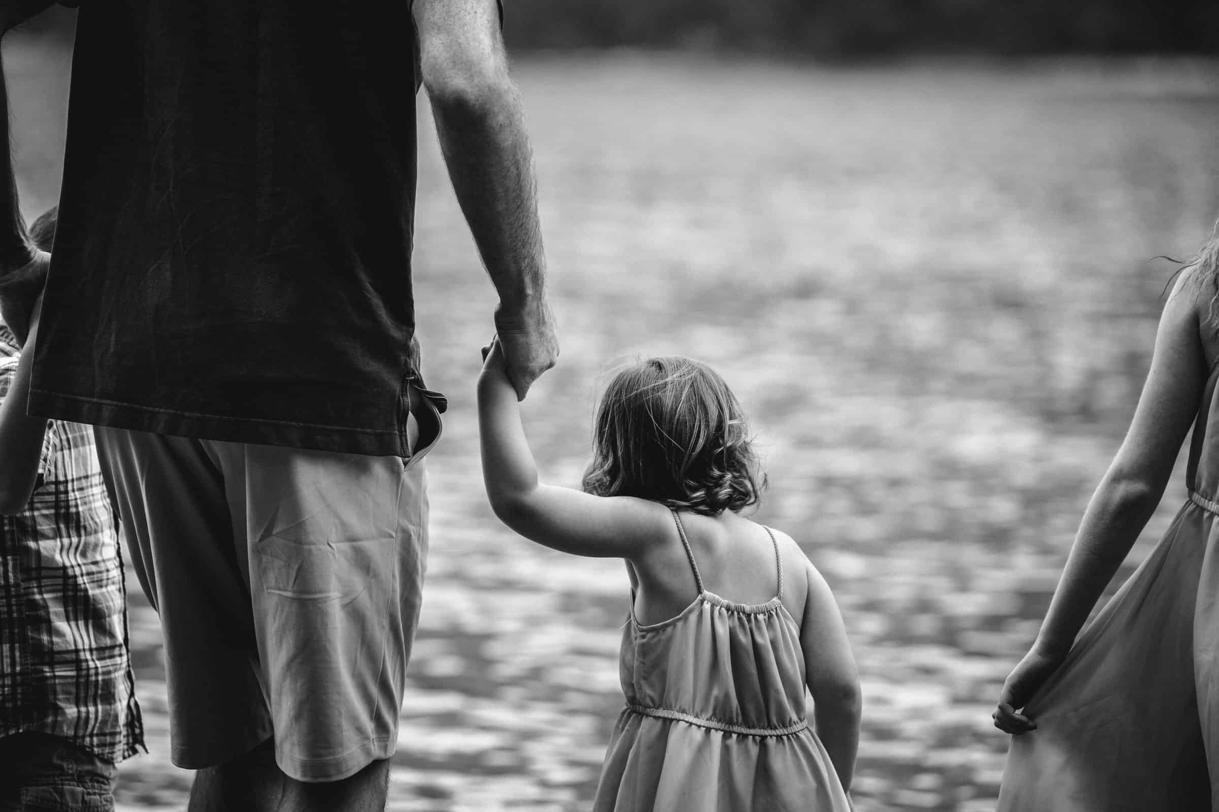 black and white image of close up of father holding daughter's hand