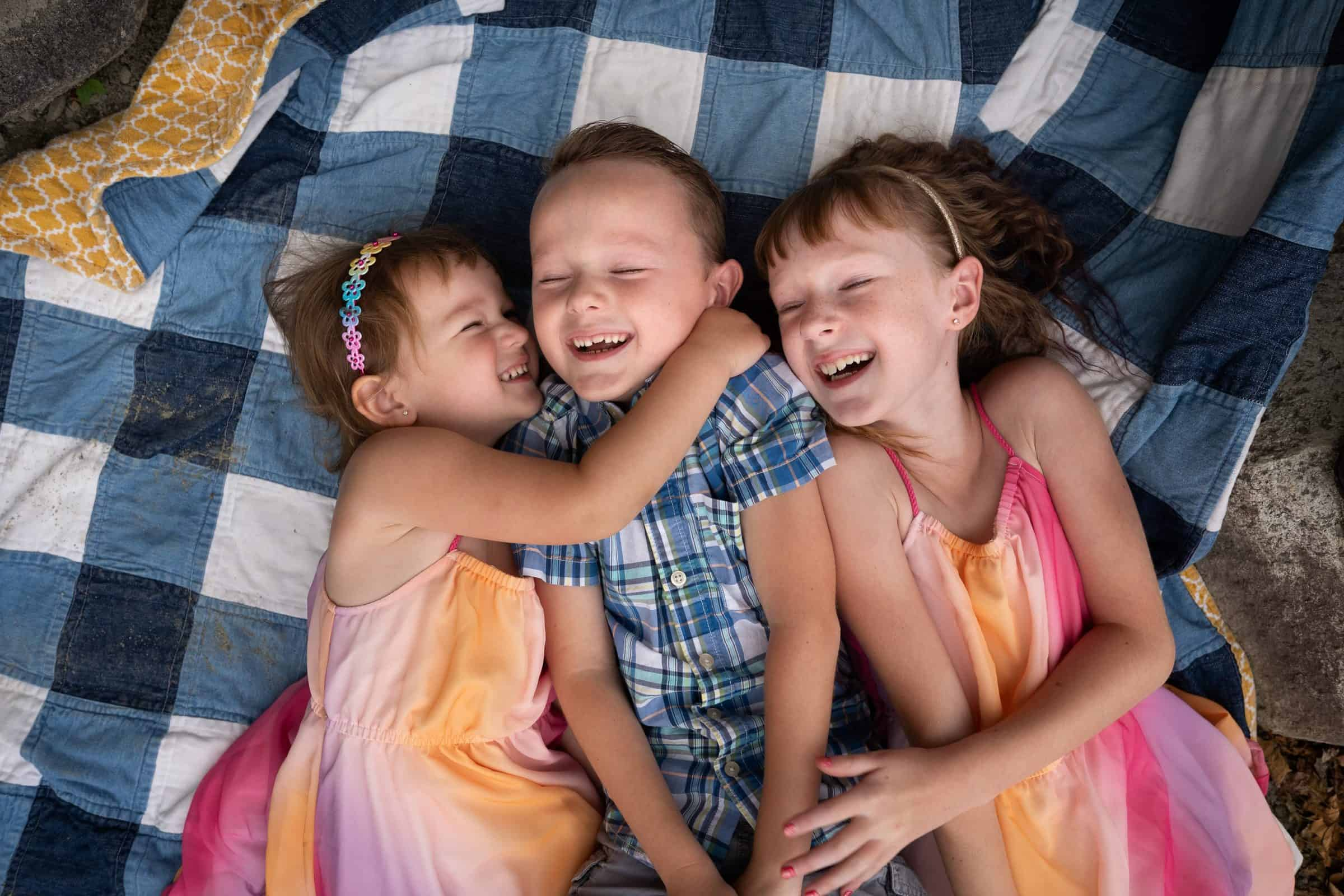 three kids laying on quilt and hugging and laughing