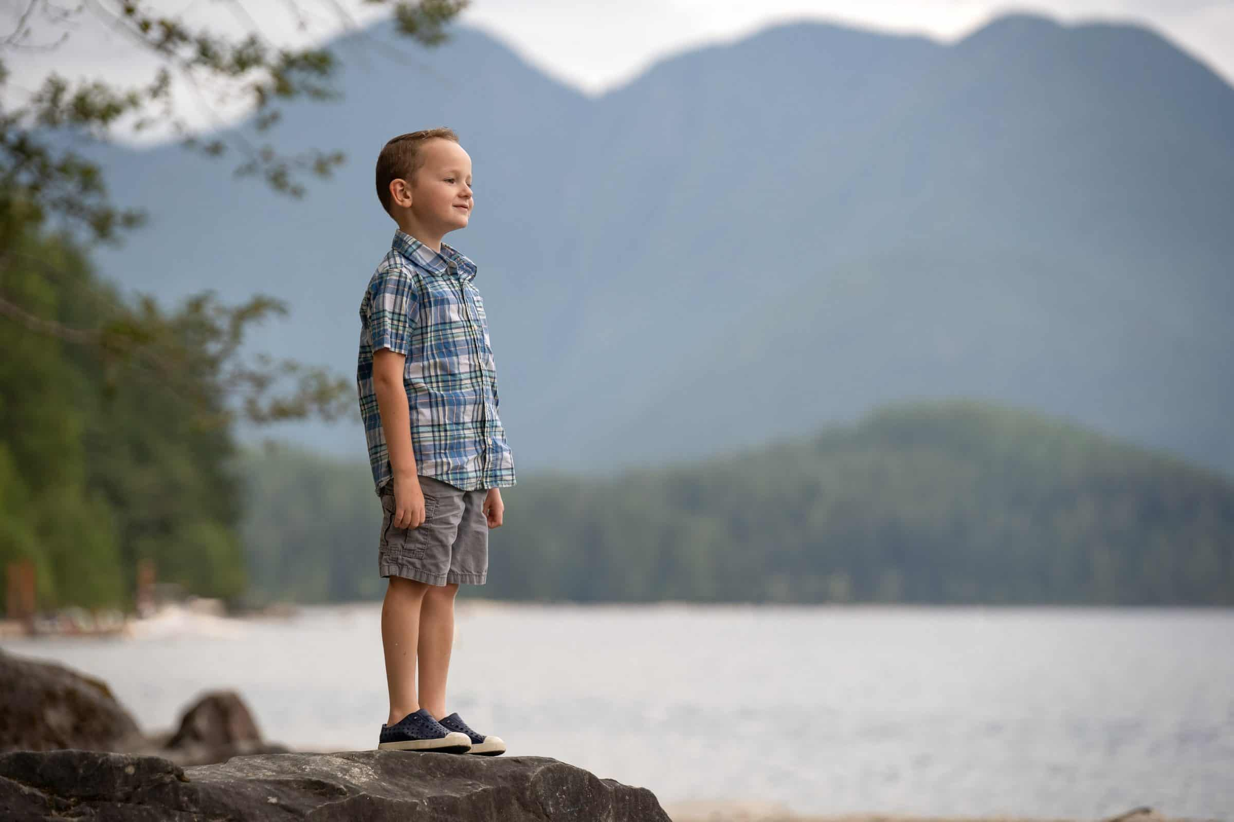 little boy standing on rocks looking out over the lake and mountains