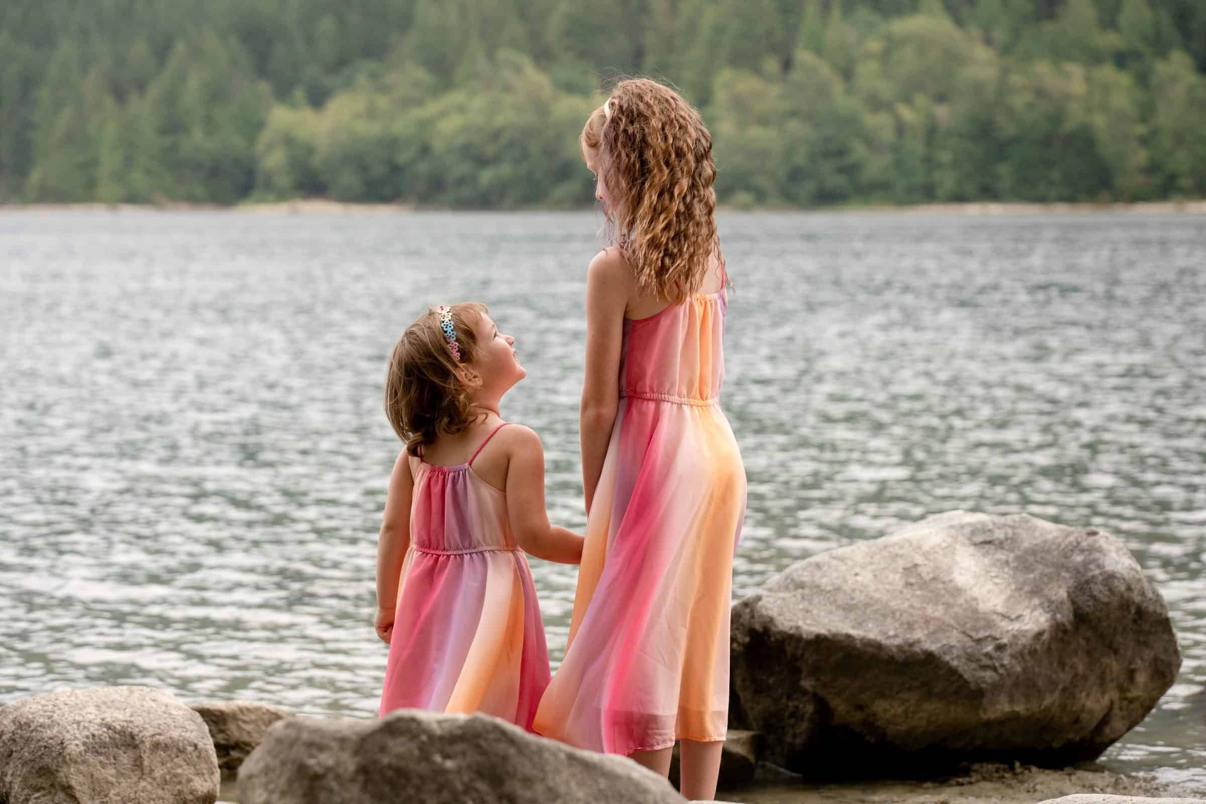 two sisters in matching dressing holding hands and looking at each other by lake