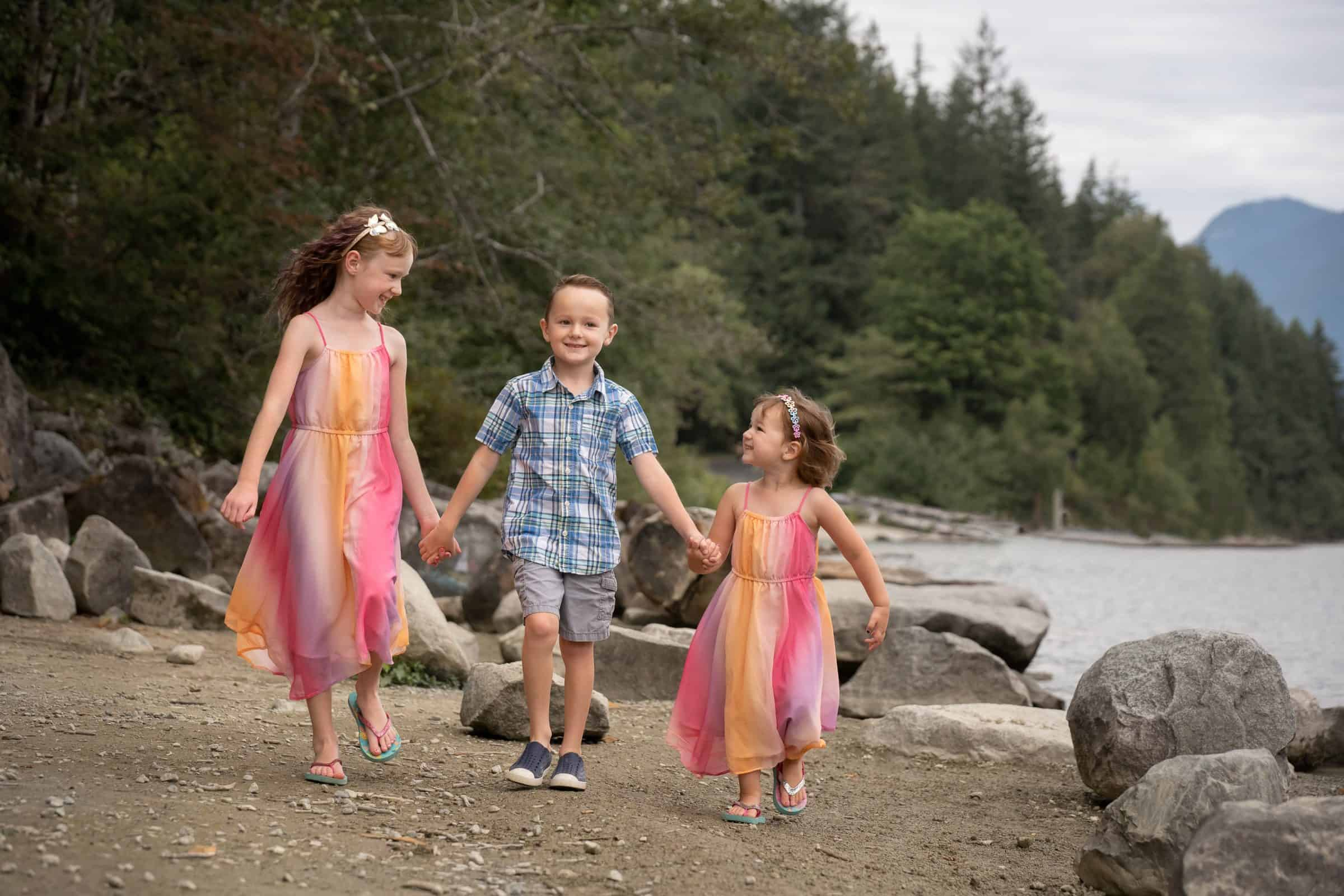 three kids holding hands and walking along beach