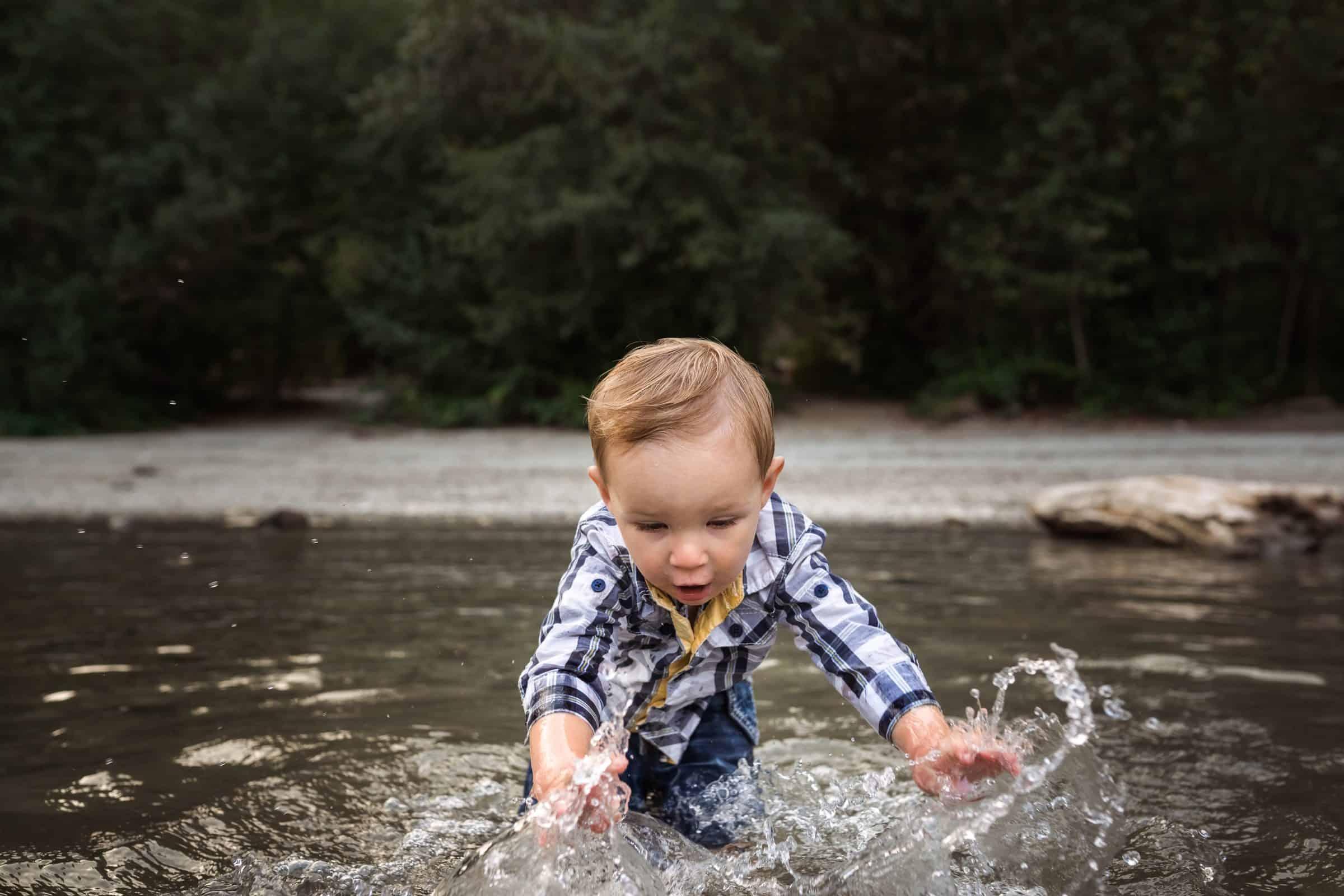 toddler boy splashing in lake