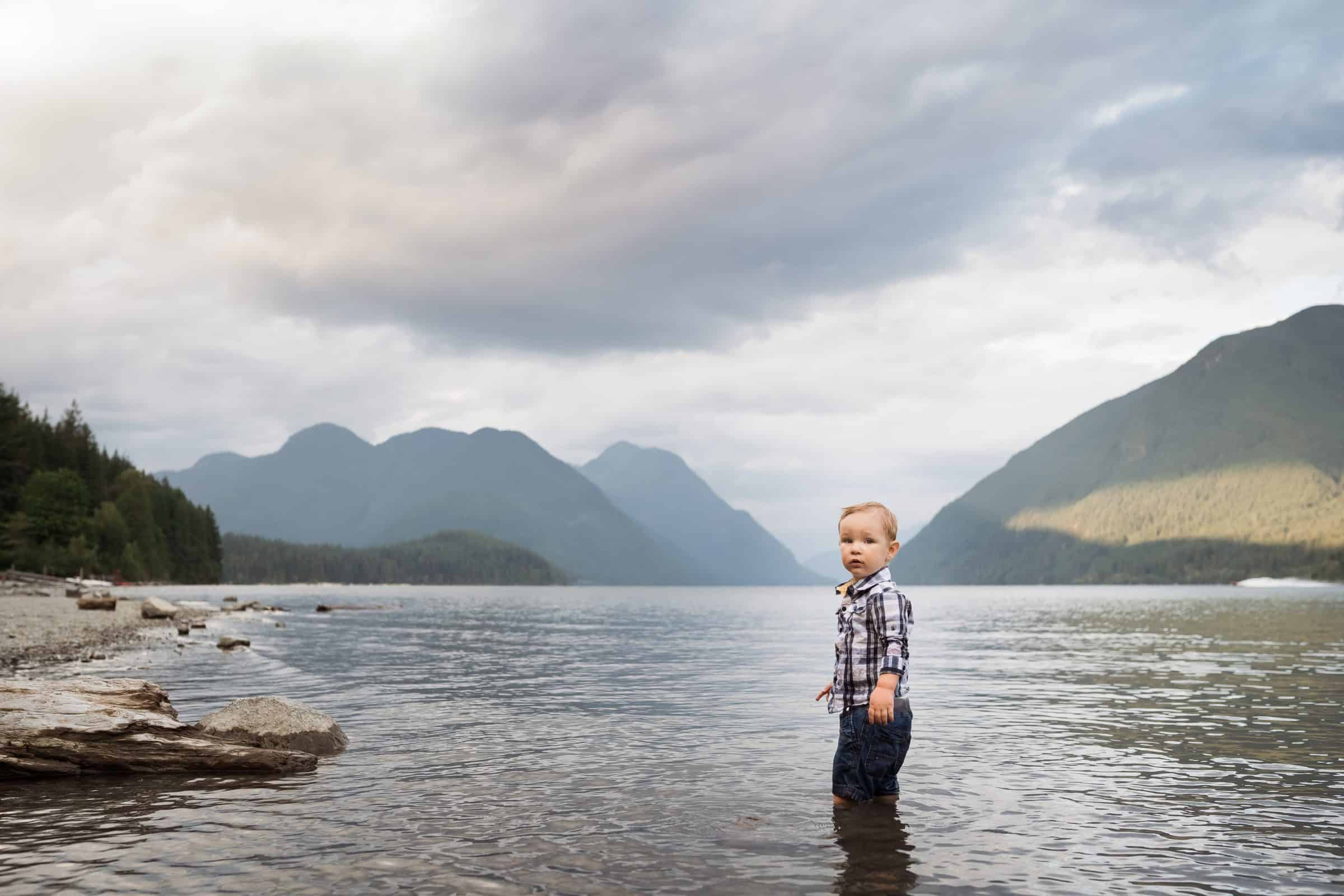 toddler boy standing in lake with mountains behind him looking at camera
